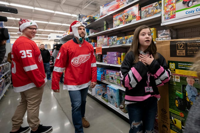 Red Wings goalie Jimmy Howard and forward Luke Glendening go shopping with twelve-year-old Ava Rekuc, of Gibraltar, during the team's annual Hometown Holiday Assist shopping spree at the Meijer on Grand River in Detroit, December 3, 2018. Several children who play hockey for  the Trenton Hockey Association were taken on a shopping trip through the store for gifts to be donated to the Children's Hospital of Michigan's Snowpile program. Later, the kids were treated to a shopping spree for themselves.