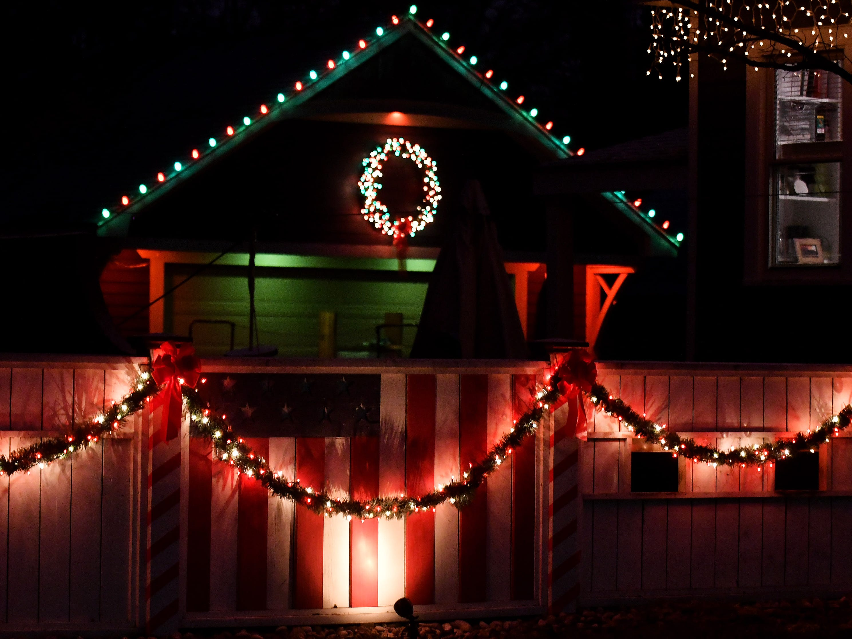 An American flag is illuminated by holiday lights, along with a garage and home in Royal Oak on Dec. 3, 2018.