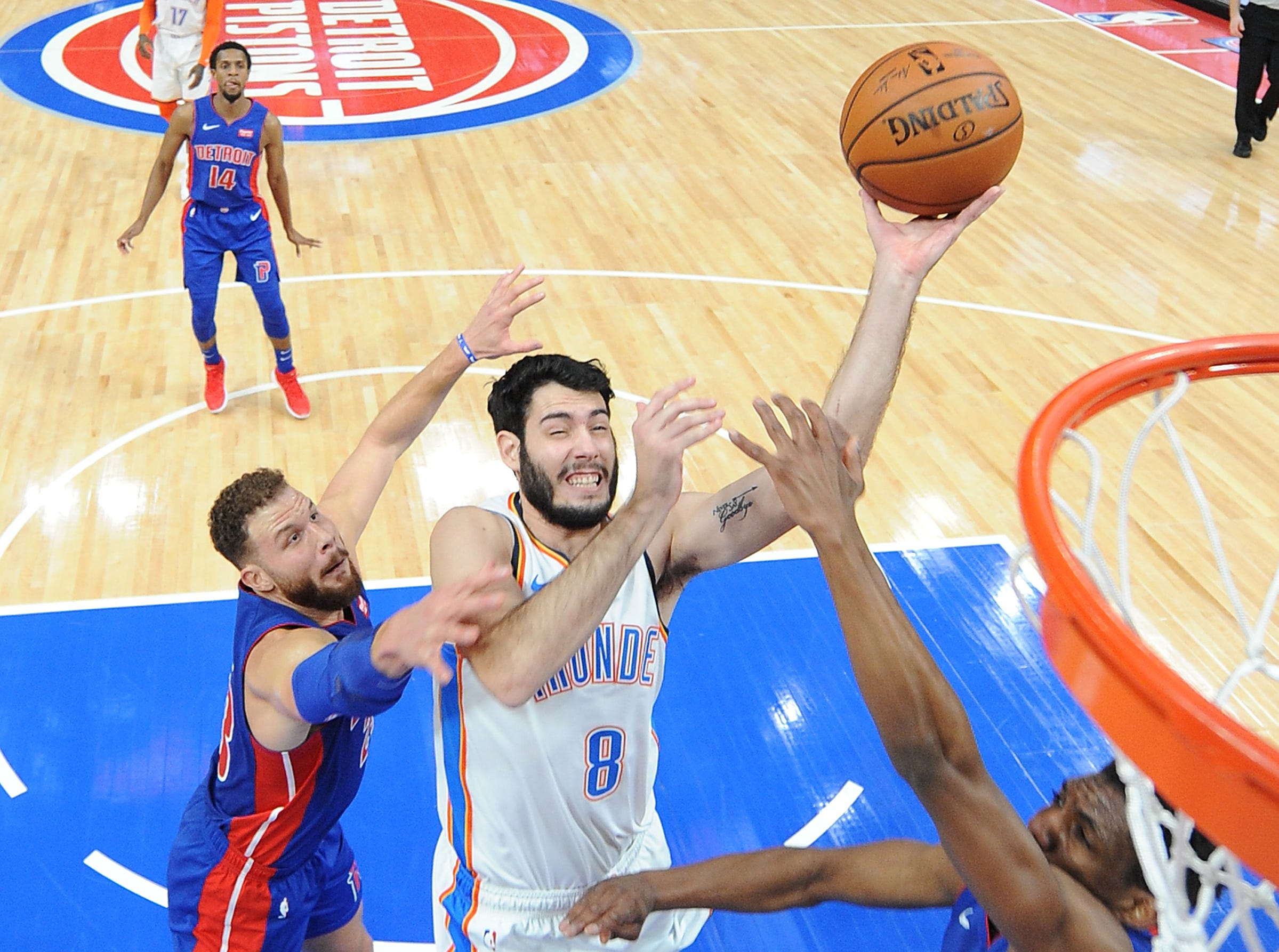 Thunder's Alex Abrines scores over Pistons' Langston Galloway and Blake Griffin in the second quarter.