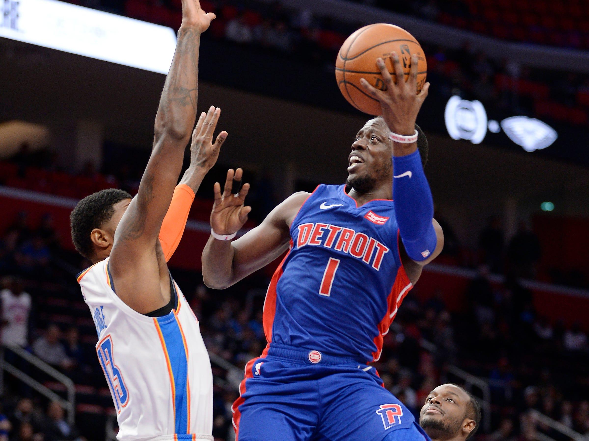 Pistons' Reggie Jackson scores over Oklahoma City Thunder's Paul George in the first quarter.