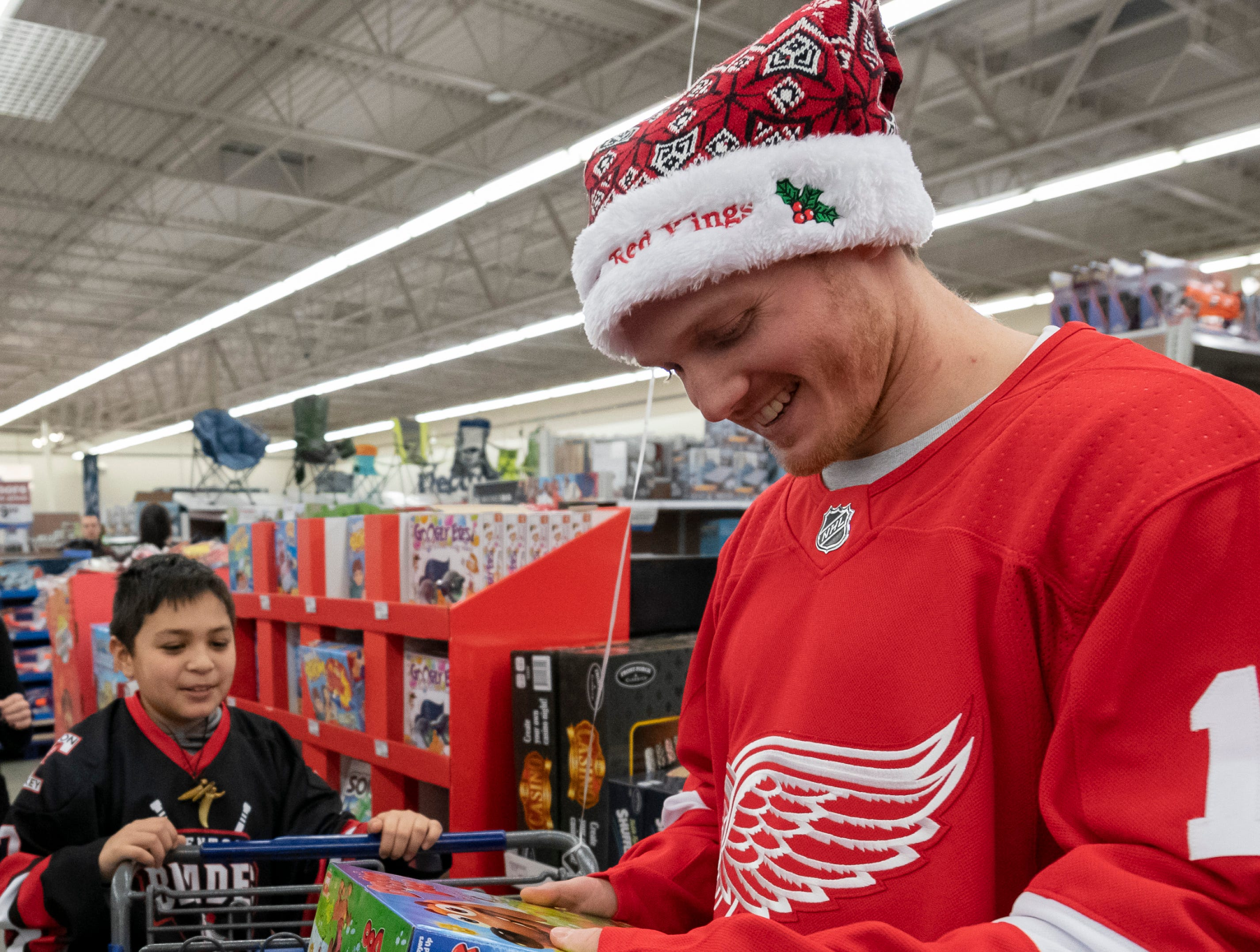 Nine-year-old Aidan Daugherty, of Brownstown, and Red Wings forward Gustav Nyquist check out toys on sale.