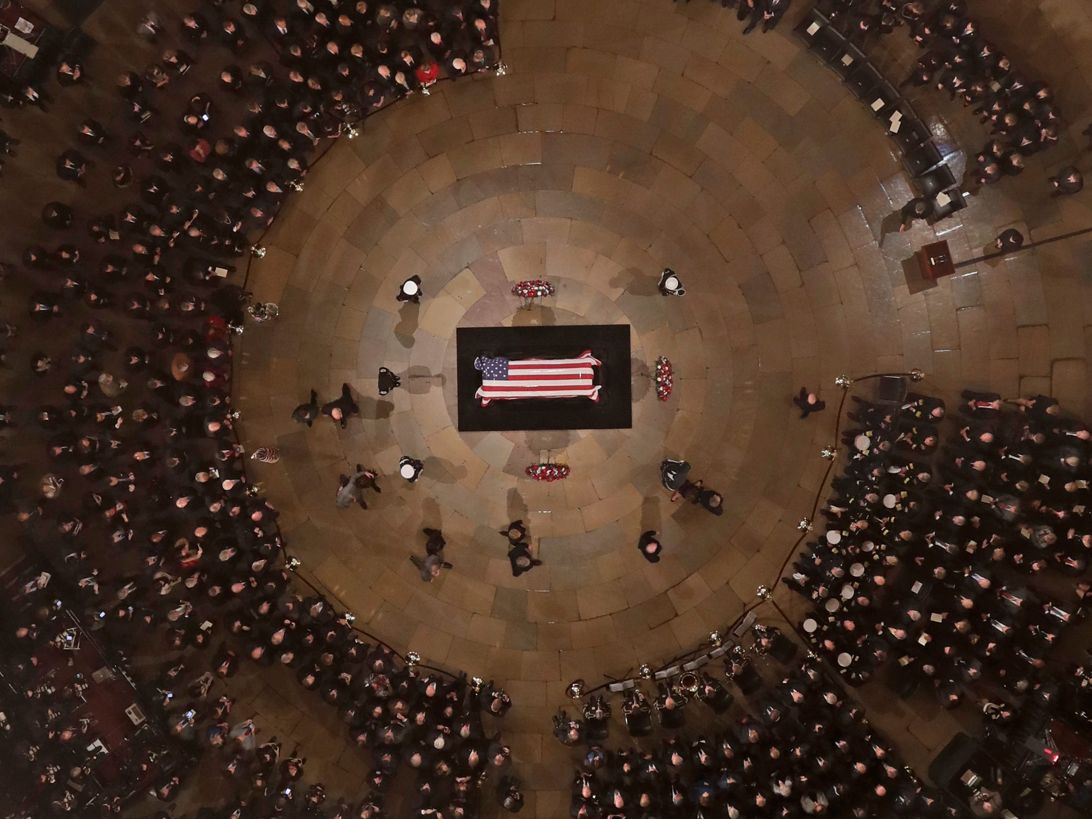 The Bush family walks past the casket of former President George H.W. Bush as he lies in state in the U.S. Capitol Rotunda.