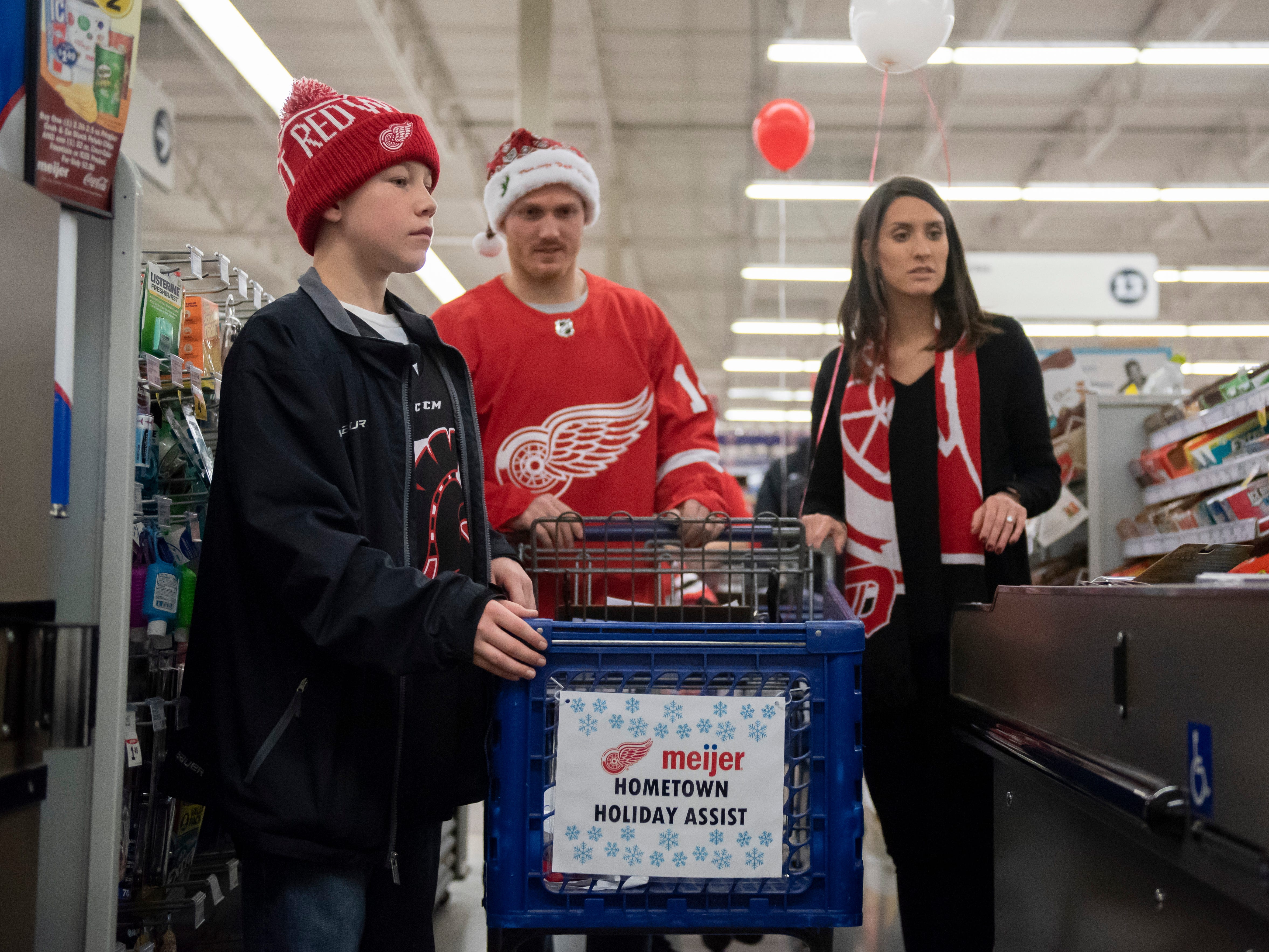 Colby Kramp, 11 of Allen Park, Red Wings center Gustav Nyquist and his wife Danielle Nyquist walk through the checkout aisle at the end of their trip.