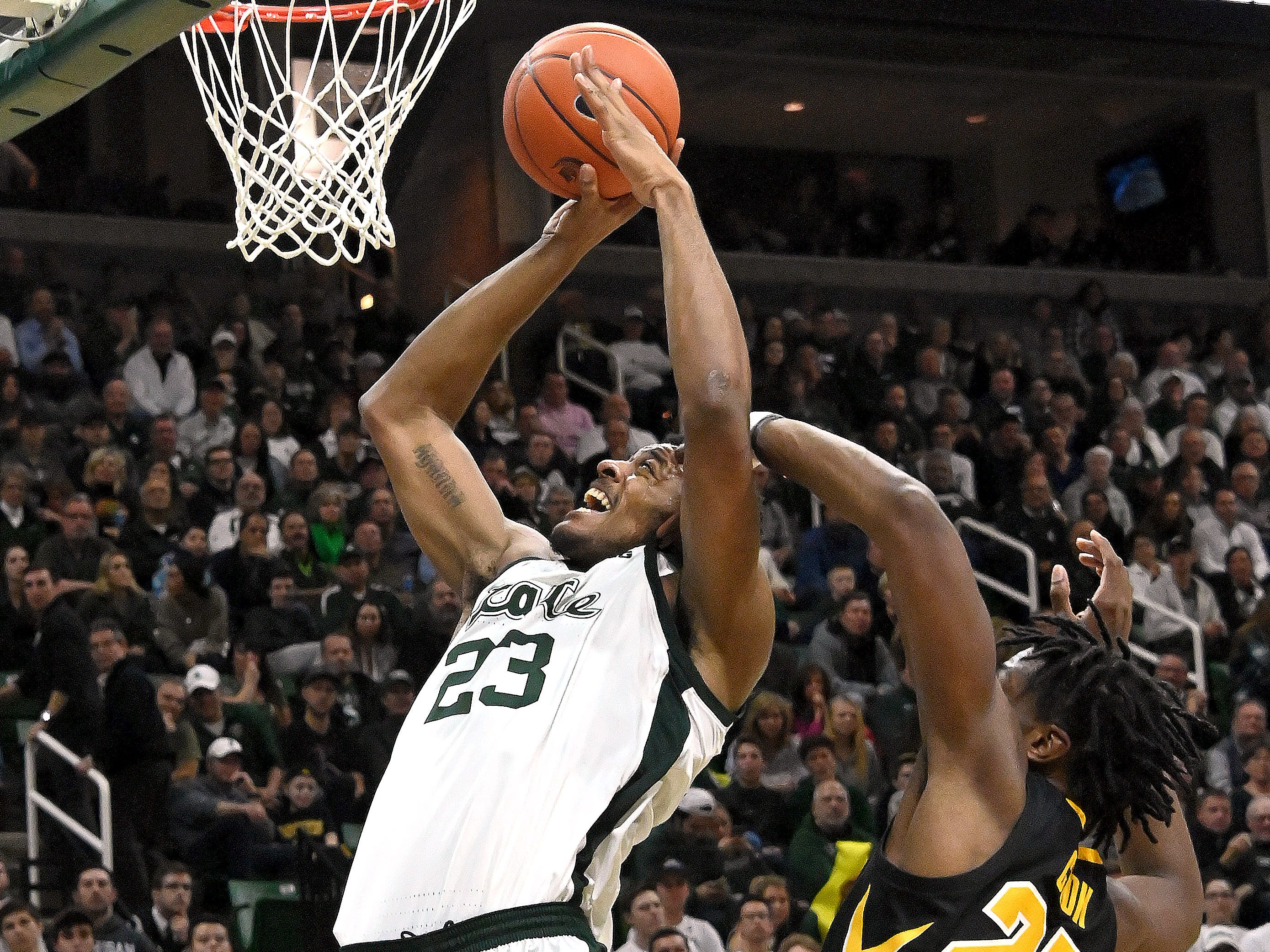 Xavier Tillman gets fouled by Tyler Cook 25) in the first half under the Spartan basket.