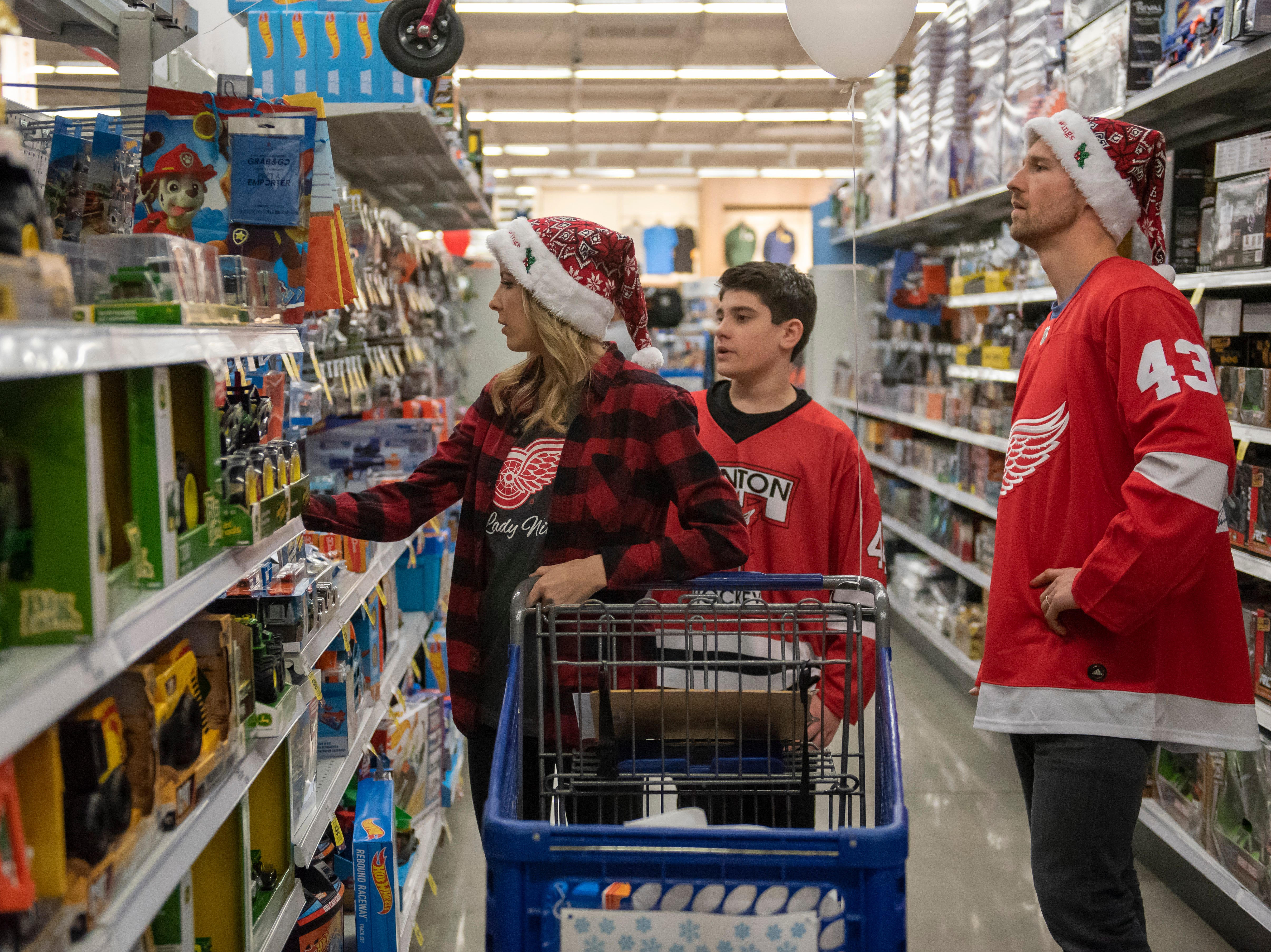 (From left) Devon Helm, thirteen-year-old Connor Giles, and Red Wings forward Darren Helm wander the aisles at Meijer.