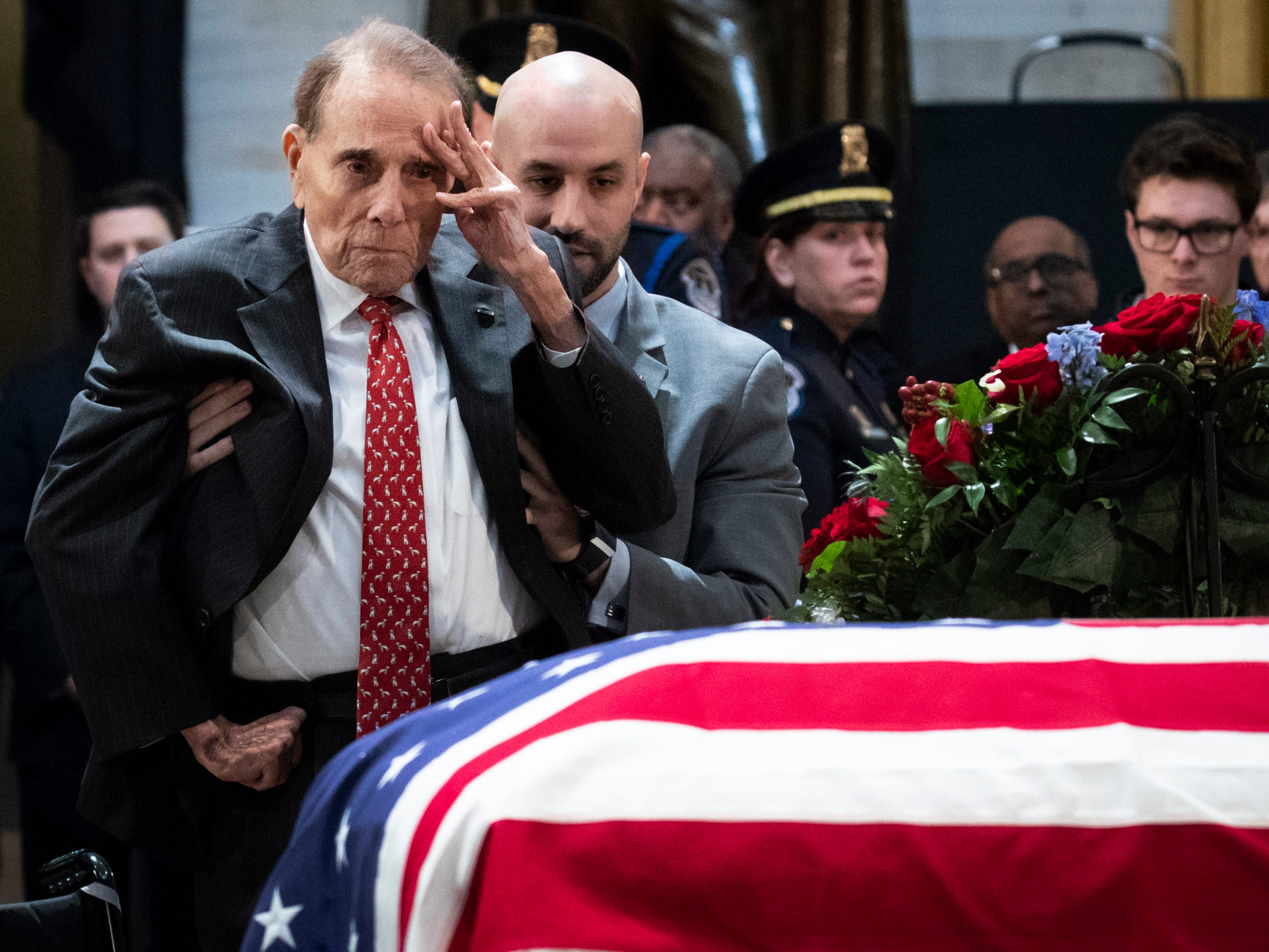Former Sen. Bob Dole stands up and salutes the casket of the late former President George H.W. Bush as he lies in state at the U.S. Capitol, December 4, 2018 in Washington, D.C. A World War II combat veteran, Bush served as a member of Congress from Texas, ambassador to the United Nations, director of the CIA, vice president and 41st president of the United States.