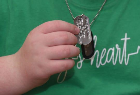 Kaleb Klakulak wears a dog tag in memory  of his best friend K.J. Singleton, who died of cancer last year.