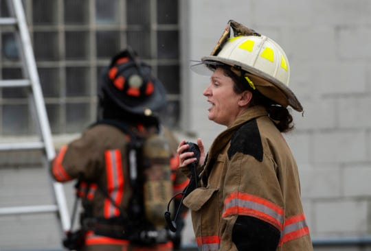 Evansville firefighter Amy Smith coordinates her team at a fire at 1652 N. Fares Avenue at about 10:40 a.m. Tuesday. The flash fire was started accidentally by a worker who was working on a truck. The building houses the Dyna-Mechs Truck Service at 1650 N. Fares. Nobody was injured in the fire.