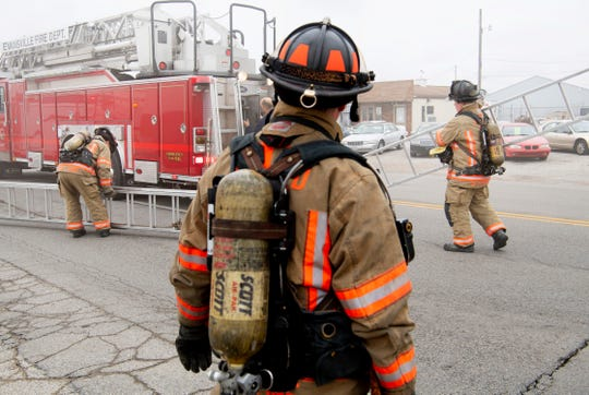 Evansville firefighters haul ladders to take on a fire at 1652 N. Fares Avenue at about 10:40 a.m. Tuesday. The flash fire was started accidentally by a worker who was working on a truck. The building houses the Dyna-Mechs Truck Service at 1650 N. Fares. Nobody was injured in the fire.