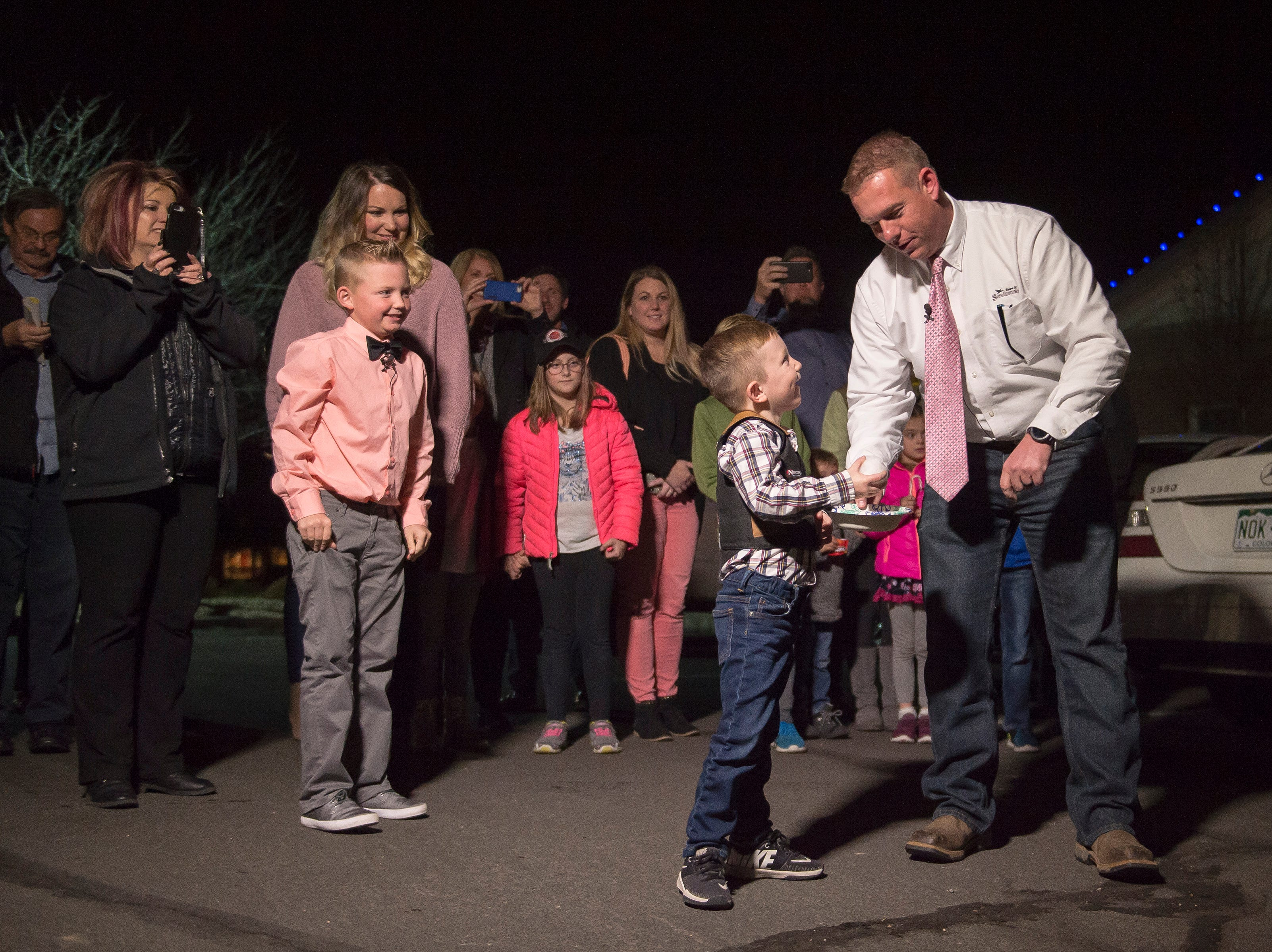 Range View Elementary School third grader Dane Best, left, looks on as his younger brother Dax is handed a second snowball, to be thrown legally, by Mayor Donald McLeod in the parking lot of the Town Hall after Dane presenting his argument to the town board trustees to change a law in Severance that bans snowball fights on Monday, Dec. 3, 2018, at the Town Hall in Severance, Colo. The board voted unanimously to approve the law change.