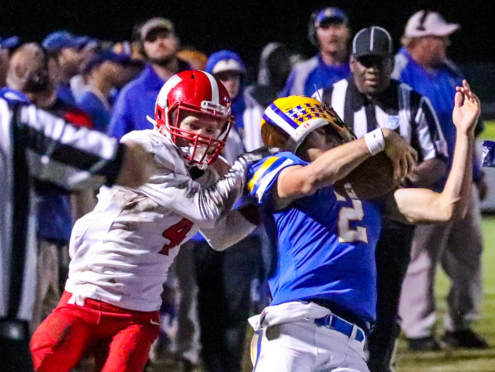 North's Clayton Savinsky rips the helmet of Charlotte quarterback Alex Muse as he brings him down. North Fort Myers played at Charlotte in their regional semifinal. North won 36-20 and will play Naples in next week's game.