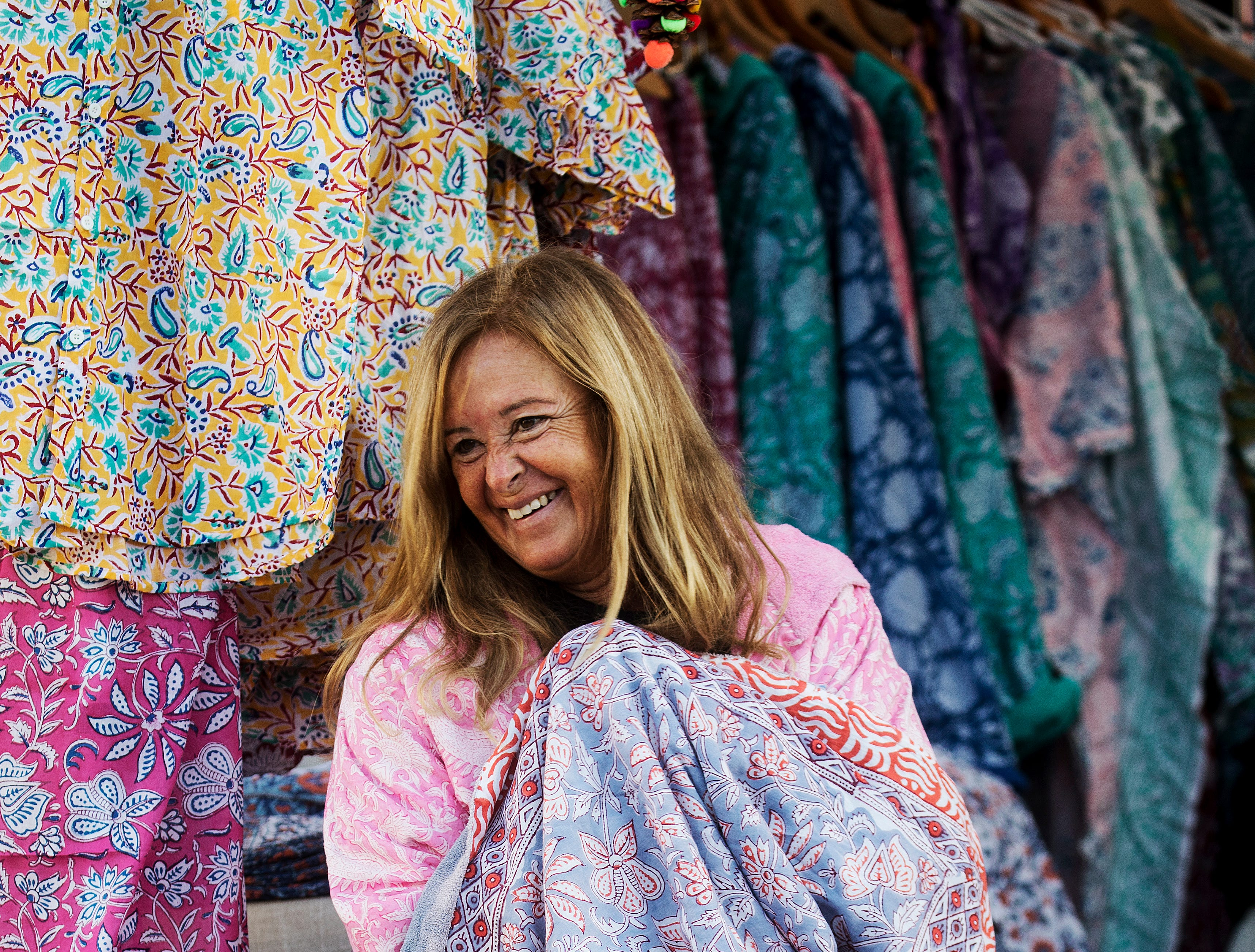 "Nancy Davis, of Holicow, a resort wear business, bundles up while waiting for customers at the Beach Baptist Farmers Market on Fort Myers Beach on Wednesday 11/28/2018. A cold front has made its way to Southwest Florida. Temps are in the 40's and 50's. The farmers market runs from October to May and is located at the Beach Baptist Church on Wednesdays from 8-1 and at Santini Plaza on Tuesday's and Thursdays from 8-1. Davis said "" It's very cold this morning, I'm waiting for the sun to come around the corner."""