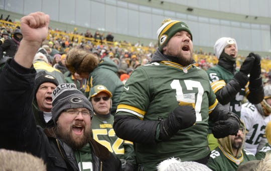 Adam Koenig of Madison, left, Chris Knutson of Howard, behind Koenig, Paul Reinhard of Howard, standing center, and Chad Bubolz of De Pere, in white hat, cheer the Green Bay Packers against the Arizona Cardinals on Dec. 2.