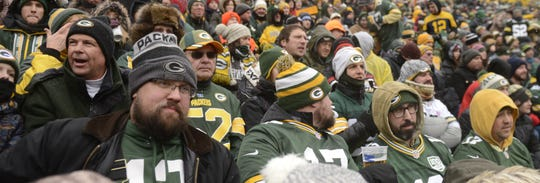 Two rows of season-ticket-holder friends in Section 103 of Lambeau Field watch the Green Bay Packers play the Arizona Cardinals on Dec. 2, 2018.