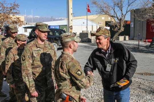 Sen. Steve Daines, right, hands out a packet of Montana-made jerky recently to a member of the 495th Combat Sustainment Support Battalion in Afghanistan.