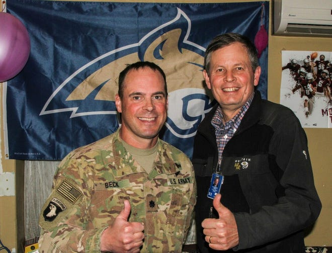 Lt. Col. Mike Beck, a Great Falls teacher, left, roots for the Bobcats with Sen Steve Daines.