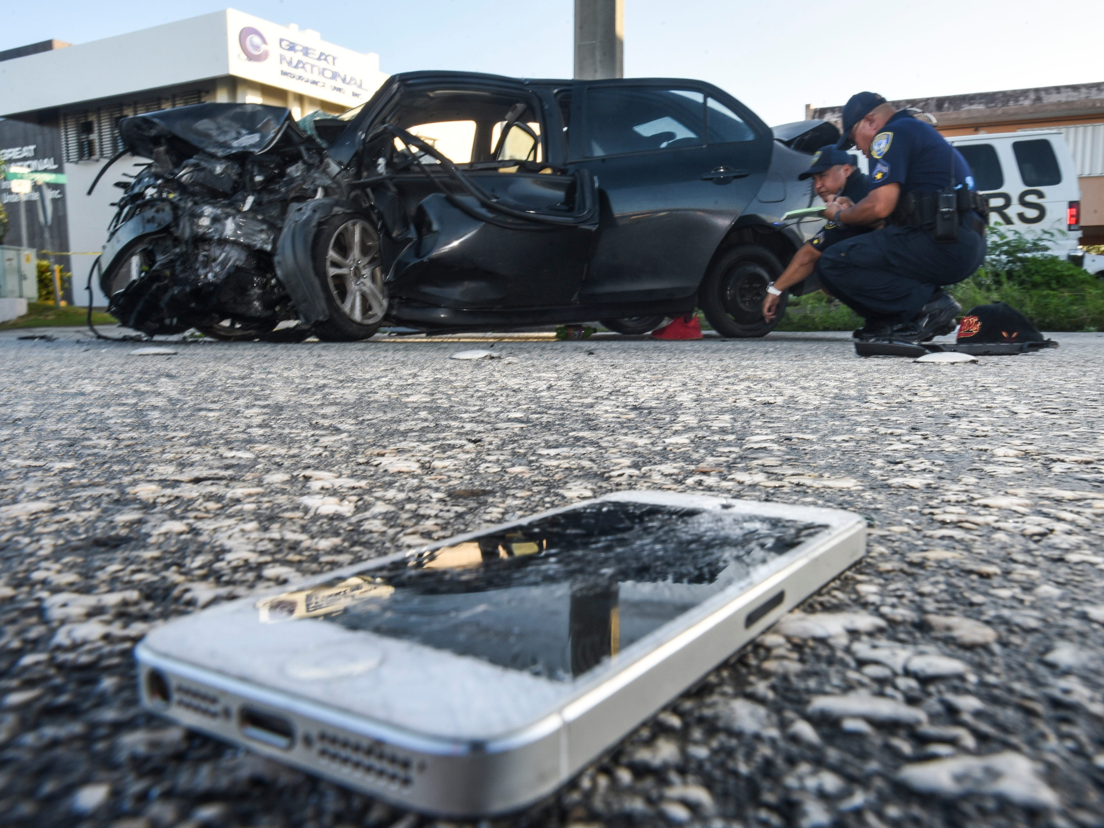 A shattered mobile phone lays on the asphalt at the scene where officers of the Guam Police Department's Highway Patrol Division investigate a fatal auto-off roadway incident, near the JNS Divers shop, on Chalan San Antonio in Tamuning on Wednesday, Dec. 5, 2018. The accident claimed the life of the driver, who was the sole occupant, after the vehicle collided into a concrete utility pole on the side of the roadway. The man's death marks the 22nd fatality and the 20th fatal crash that has occured this year.