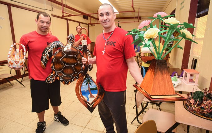Department of Corrections inmate Tresean Ramey, left, holds a 3D origami swan basket and sea turtle sculture as fellow inmate, Ken Manibusan, shows his Guam seal hook and floral arrangement art pieces during a media event at the correctional facility in Mangilao on Tuesday, Dec. 4, 2018. The artworks were primarily made from repurposed newspaper material, shoe polish, paint and lacquer. It and many others paper projects, were created by Ramey, Manibusan, and six inmates participating in the agency's Paper Project pilot program.