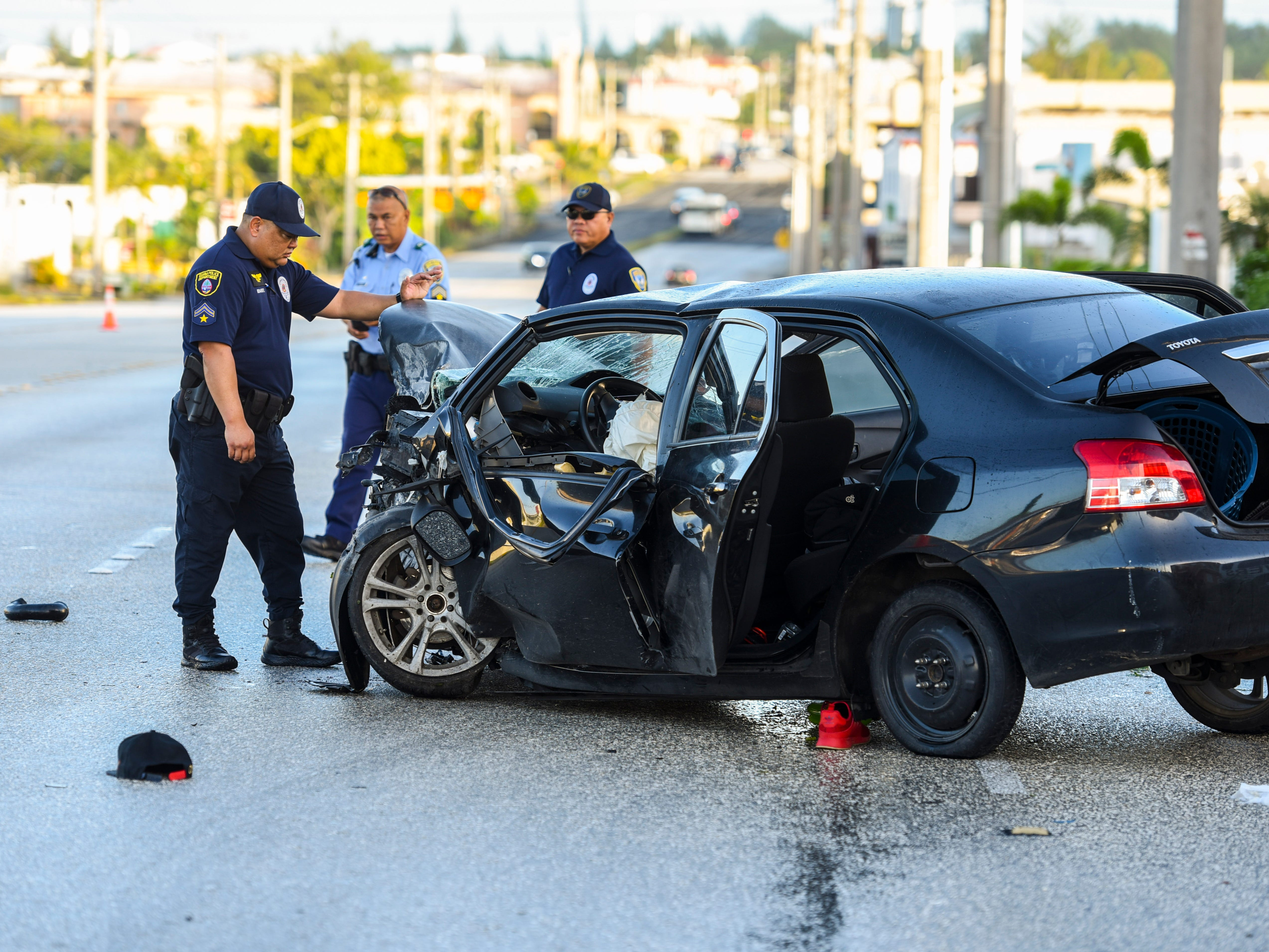 Guam Police Department Officer Tom Benavente inspects the crushed engine compartment of a black Toyota Yaris involved in a fatal auto-off roadway incident, near the JNS Divers shop on Chalan San Antonio, as he and other Highway Patrol Division officers investigate the crash in Tamuning on Wednesday, Dec. 5, 2018. The accident claimed the life of the driver, who was the sole occupant, after the vehicle collided into a concrete utility pole on the side of the roadway. The man's death marks the 22nd fatality and the 20th fatal crash that has occured this year.