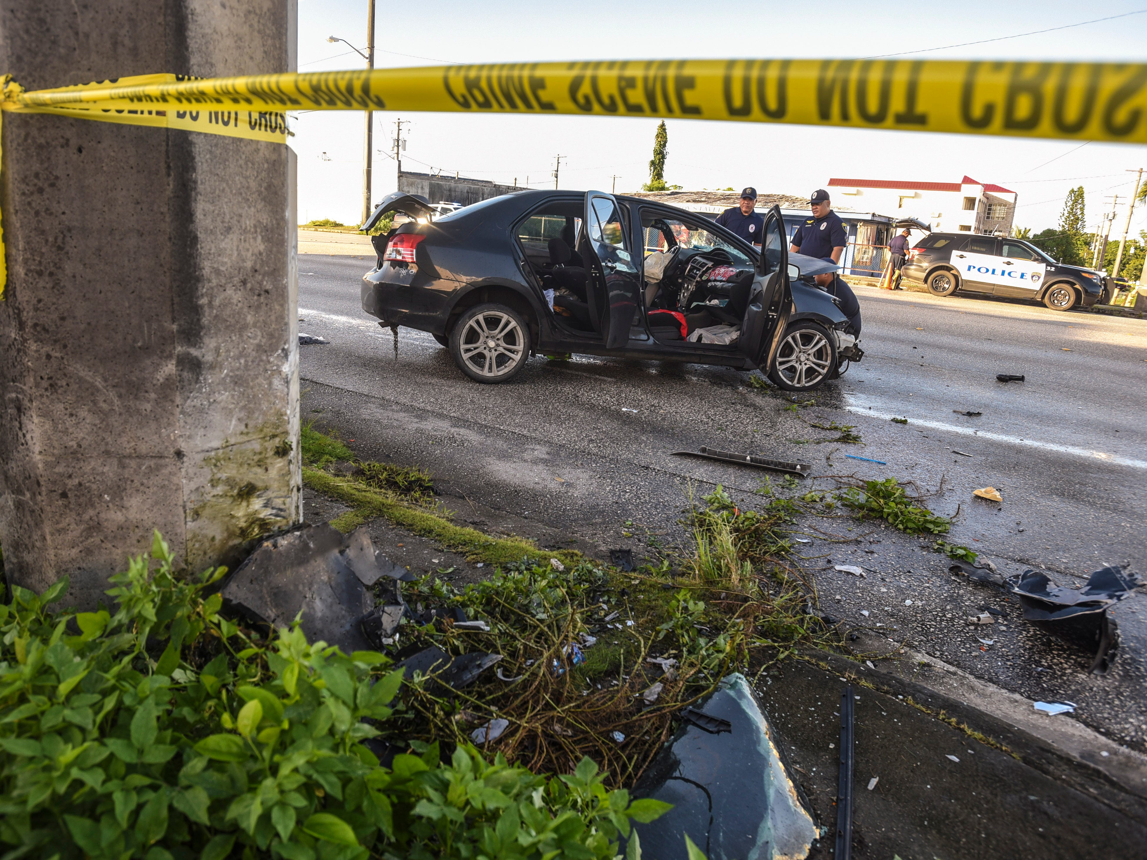 Debris from a crash remain scattered at the scene of a fatal auto-off roadway incident, near the JNS Divers shop on Chalan San Antonio, as officers with the Guam Police Department's Highway Patrol Division investigate the incident in Tamuning on Wednesday, Dec. 5, 2018. The crash claimed the life of the driver, who was the sole occupant, after the vehicle collided into a concrete utility pole on the side of the roadway. The man's death marks the 22nd fatality and the 20th fatal crash that has occured this year.