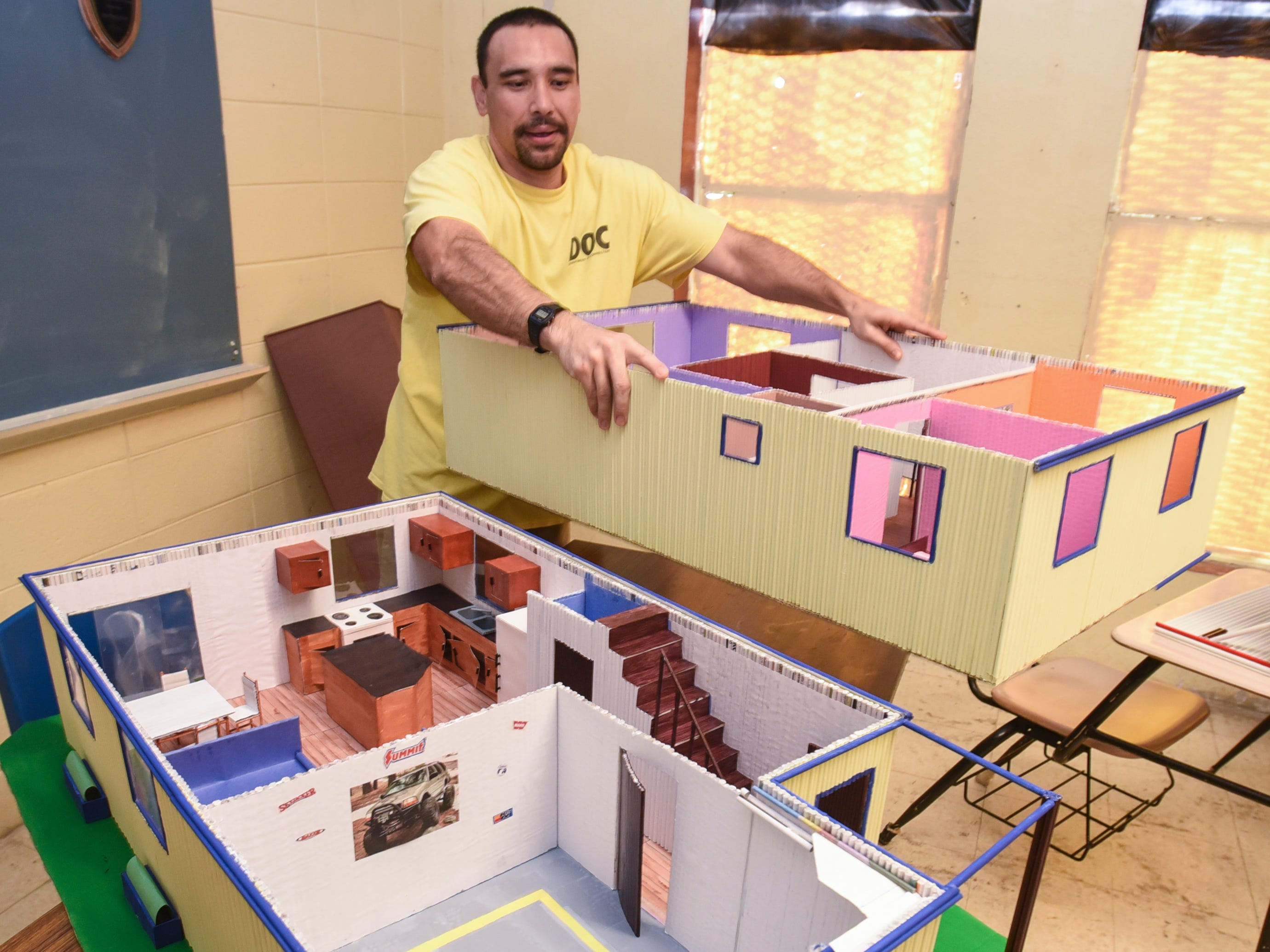 Department of Corrections inmate, Roy Pablo, separates the floors of his model two-story home to reveal it's interior layout and decor during a media event at the correctional facility in Mangilao on Tuesday, Dec. 4, 2018. The model and most of it's contents is constructed of tightly rolled newspaper material and built-to-scale model, along with some glue and paint, said Pablo.