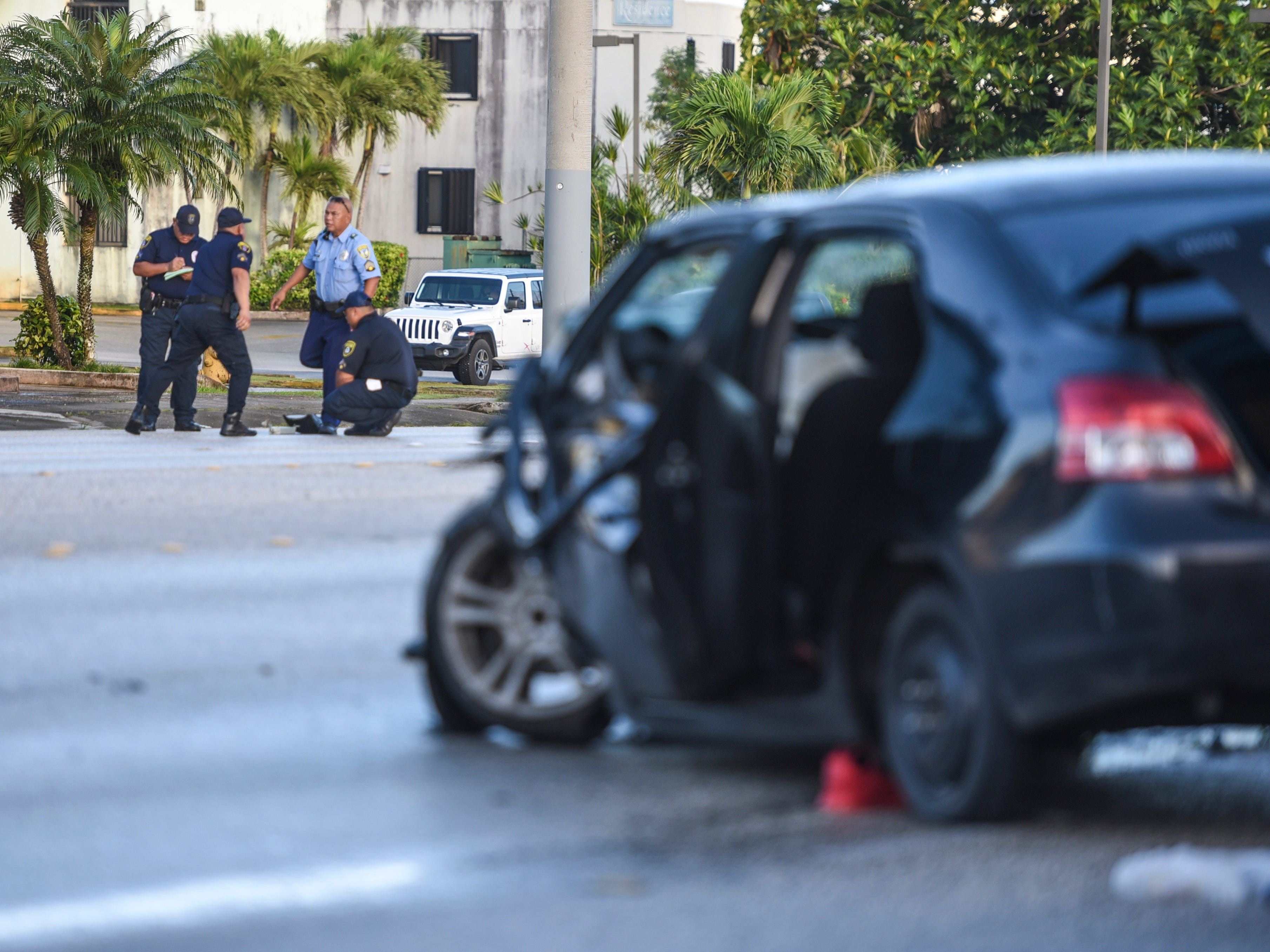 Officers with the Guam Police Department's Highway Patrol Division investigate a fatal auto-off roadway incident near the JNS Divers shop on Chalan San Antonio in Tamuning on Wednesday, Dec. 5, 2018. The accident claimed the life of the driver, who was the sole occupant, after the vehicle collided into a concrete utility pole on the side of the roadway. The man's death marks the 22nd fatality and the 20th fatal crash that has occured this year.
