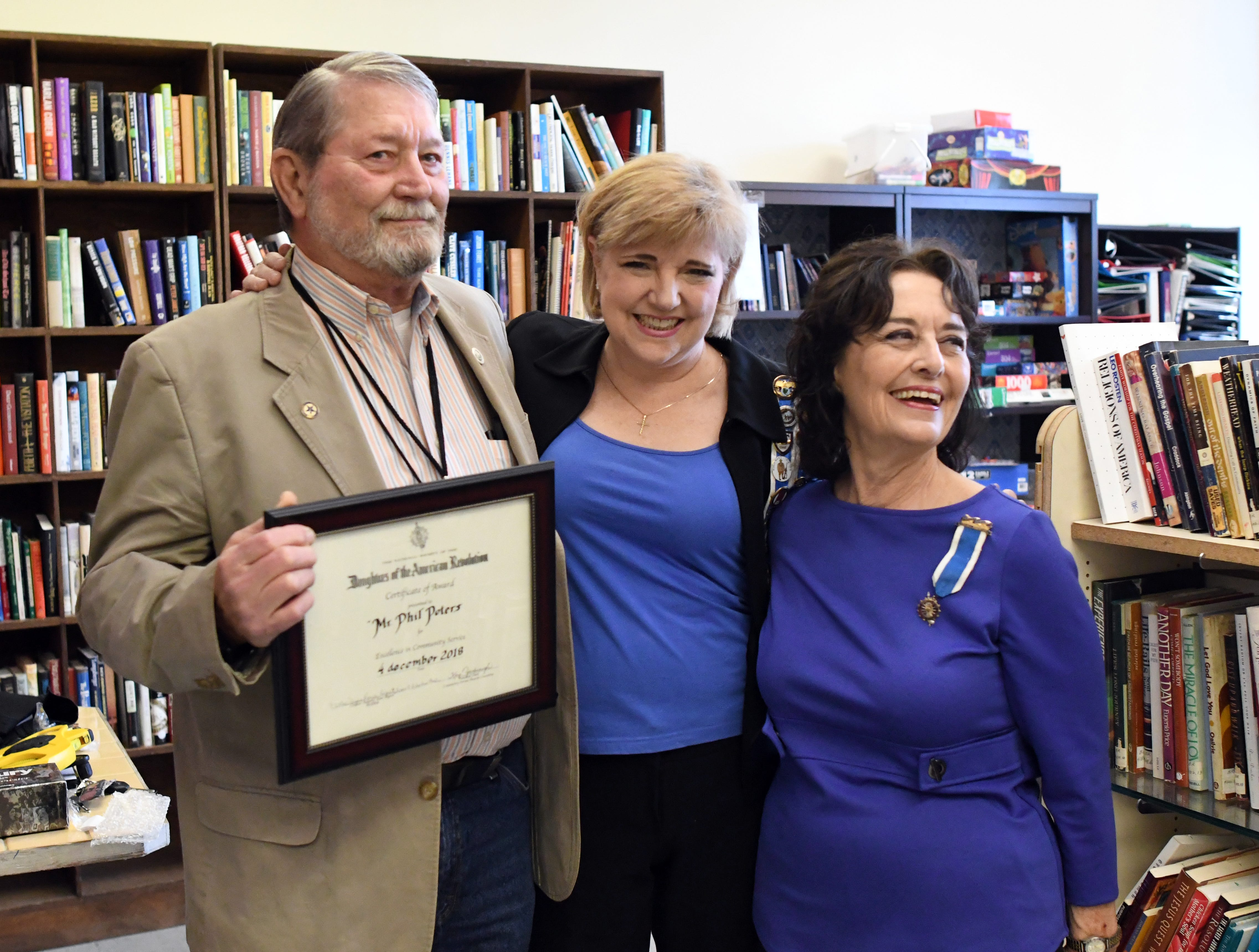 Daughters of the American Revolution members Rebekah Ray, middle, and Lynn Royse, right, surprise Phillip Peters with the community service award for his volunteering with Edward Street Fellowship Thrift Store on Tuesday, December 4, 2018. Peters has been volunteering with the store since 2002.