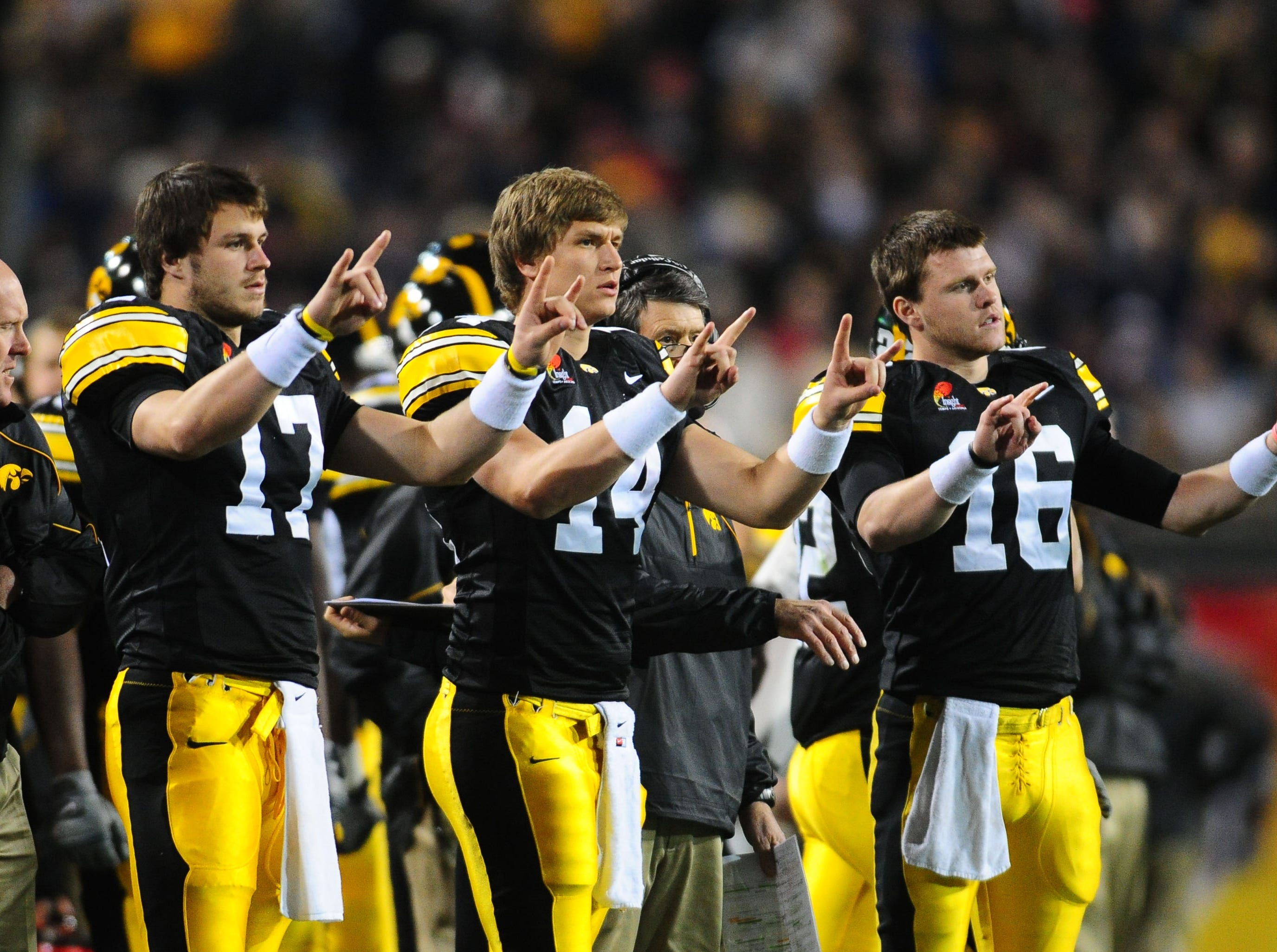Dec. 28, 2010; Tempe, AZ, USA; Iowa Hawkeyes quarterbacks (from left) A.J. Derby , John Wienke and James Vandenberg signal a play from the sidelines against the Missouri Tigers in the 2010 Insight Bowl at Sun Devil Stadium. Iowa defeated Missouri 27-24. Mandatory Credit: Mark J. Rebilas-USA TODAY Sports