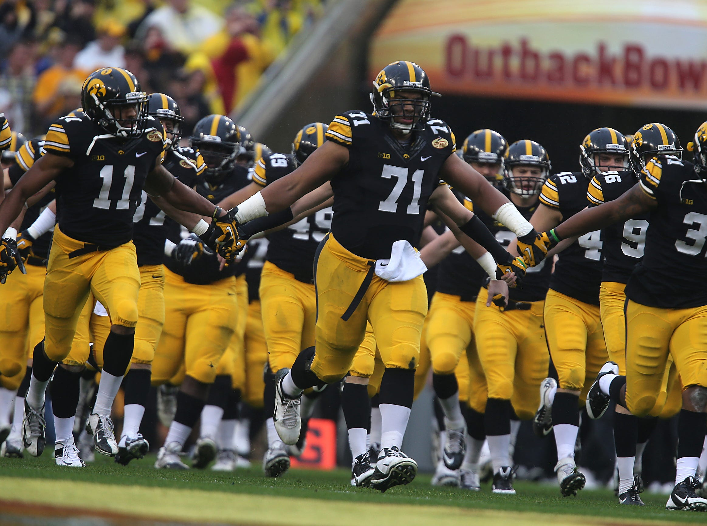 Iowa defensive lineman Carl Davis (71) and the Hawkeyes take the field prior to kickoff against LSU in the Outback Bowl on Wednesday, Jan. 1, 2014, in Tampa, Florida. (Bryon Houlgrave/The Register)