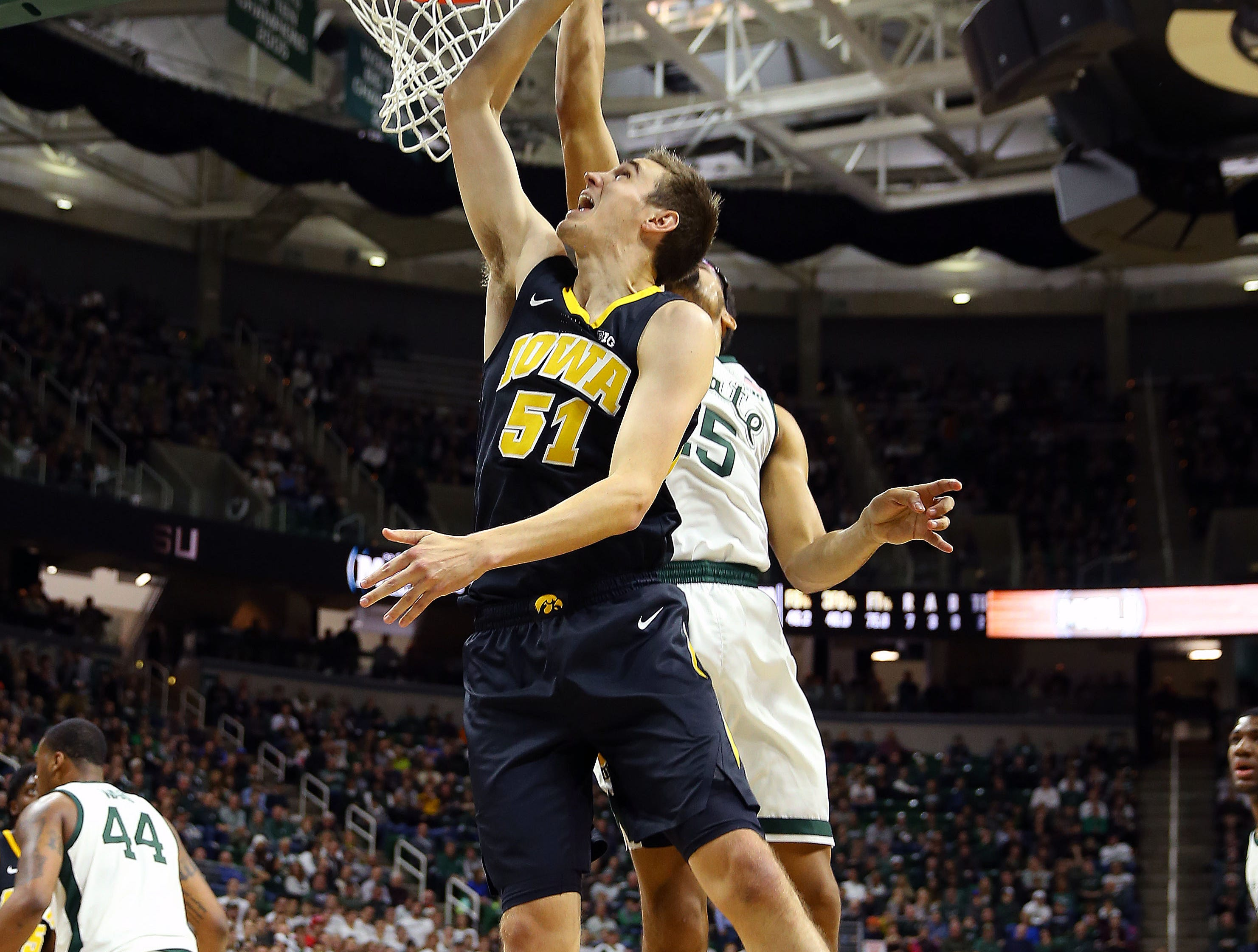 Dec 3, 2018; East Lansing, MI, USA; Iowa Hawkeyes forward Nicholas Baer (51) lays the ball up over Michigan State Spartans forward Kenny Goins (25) during the first half of a game at Breslin Center. Mandatory Credit: Mike Carter-USA TODAY Sports