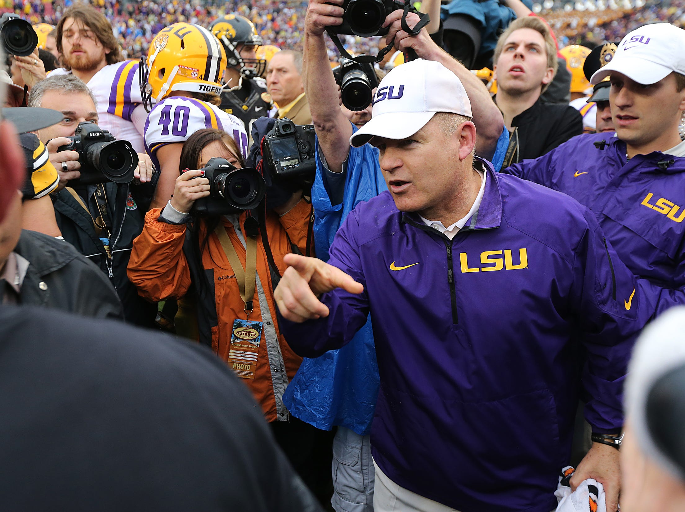 Louisiana State coach Les Miles meets with Iowa coach Kirk Ferentz following Miles and LSU's 21-14 win over the Hawkeyes on Wednesday, Jan. 1, 2014, in Tampa, Florida. (Bryon Houlgrave/The Register)