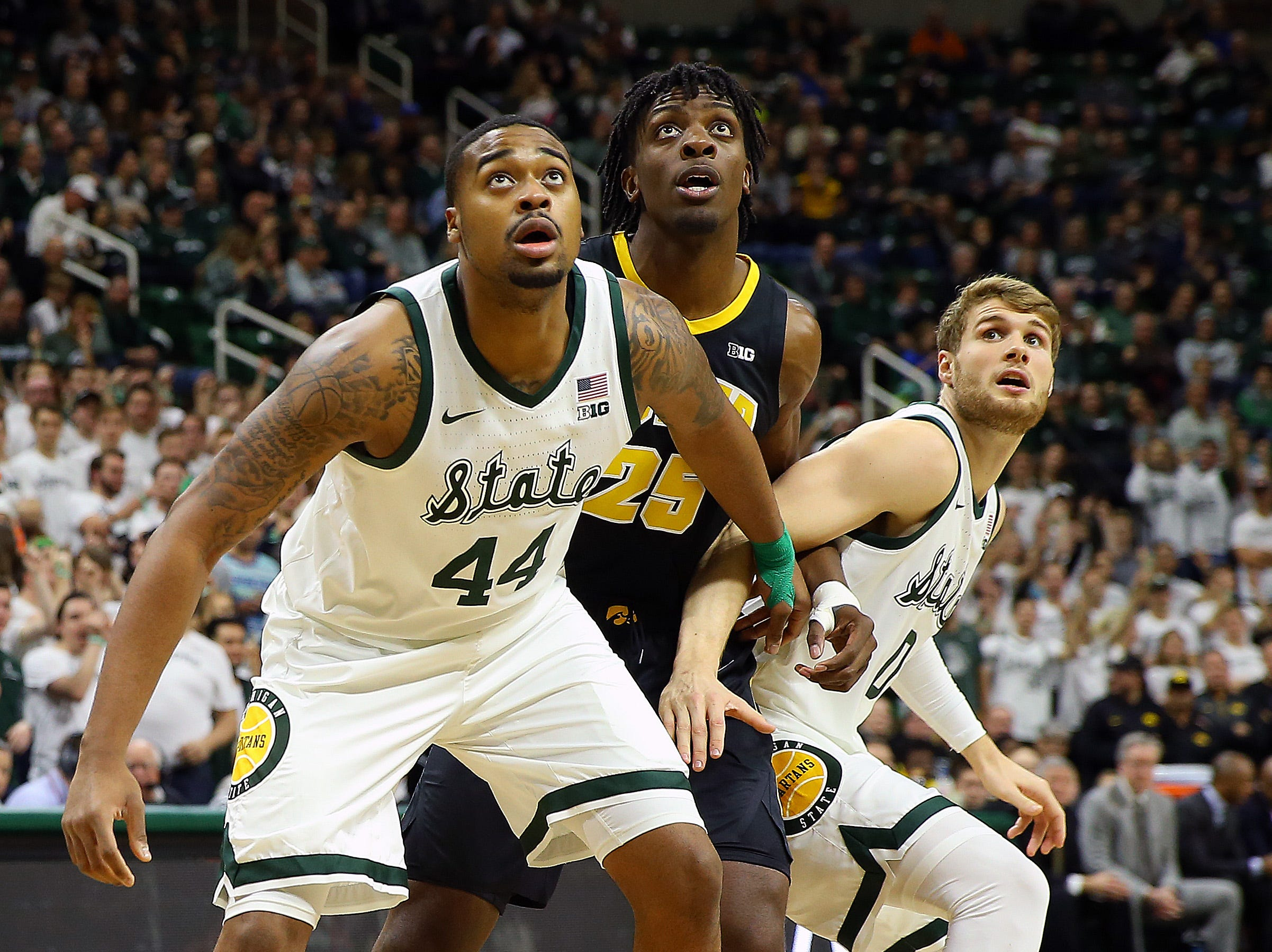 Dec 3, 2018; East Lansing, MI, USA; Michigan State Spartans forward Nick Ward (44) and Iowa Hawkeyes forward Tyler Cook (25) and Michigan State Spartans forward Kyle Ahrens (0) fight for position during the first half of a game at Breslin Center. Mandatory Credit: Mike Carter-USA TODAY Sports