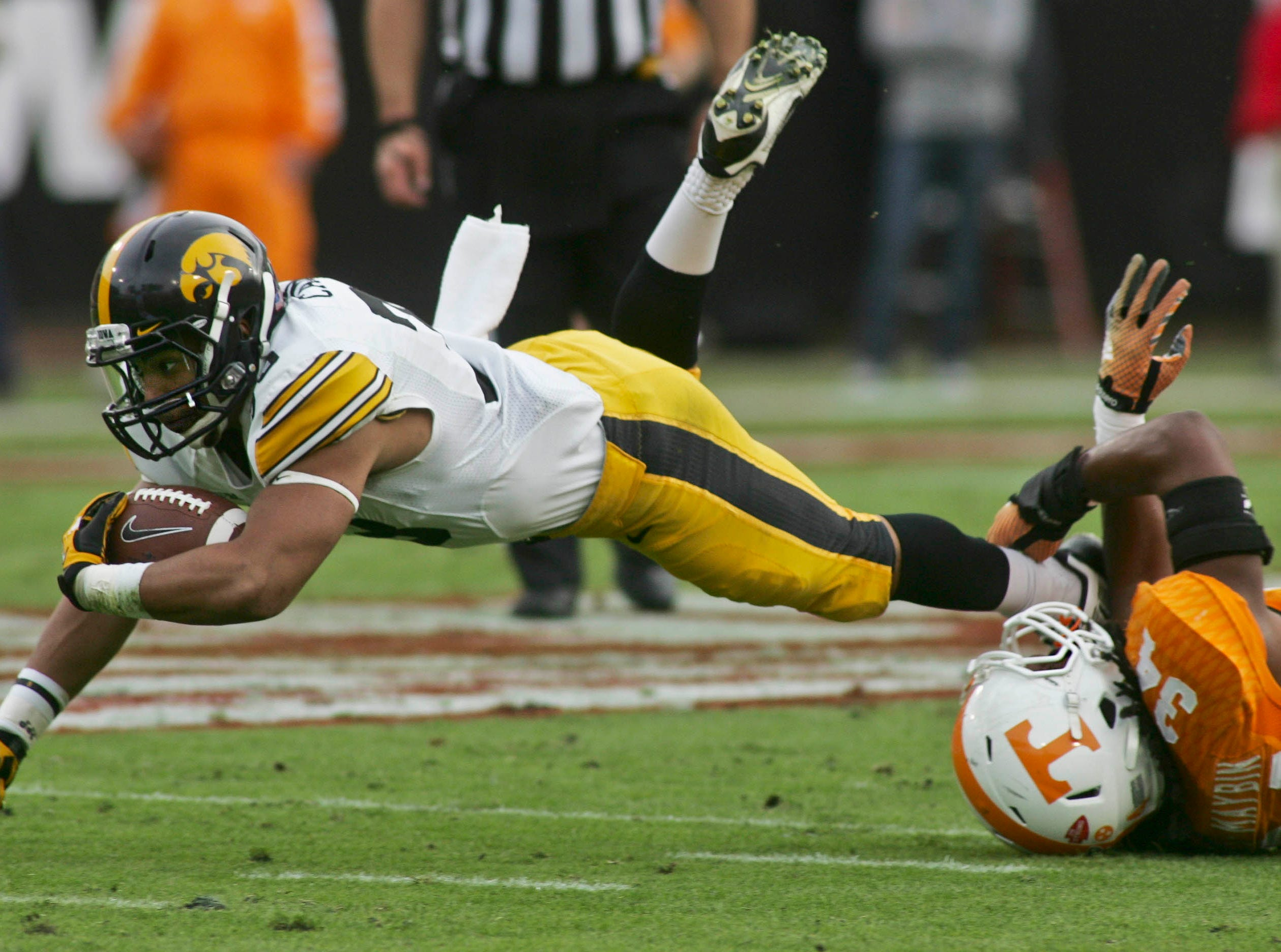 Jan 2, 2015; Jacksonville, FL, USA; Iowa Hawkeyes running back Jordan Canzeri (33) dives for extra yardage as he is tripped up by Tennessee Volunteers linebacker Jalen Reeves-Maybin (34) in the first quarter of their 2015 TaxSlayer Bowl at EverBank Field. Mandatory Credit: Phil Sears-USA TODAY Sports