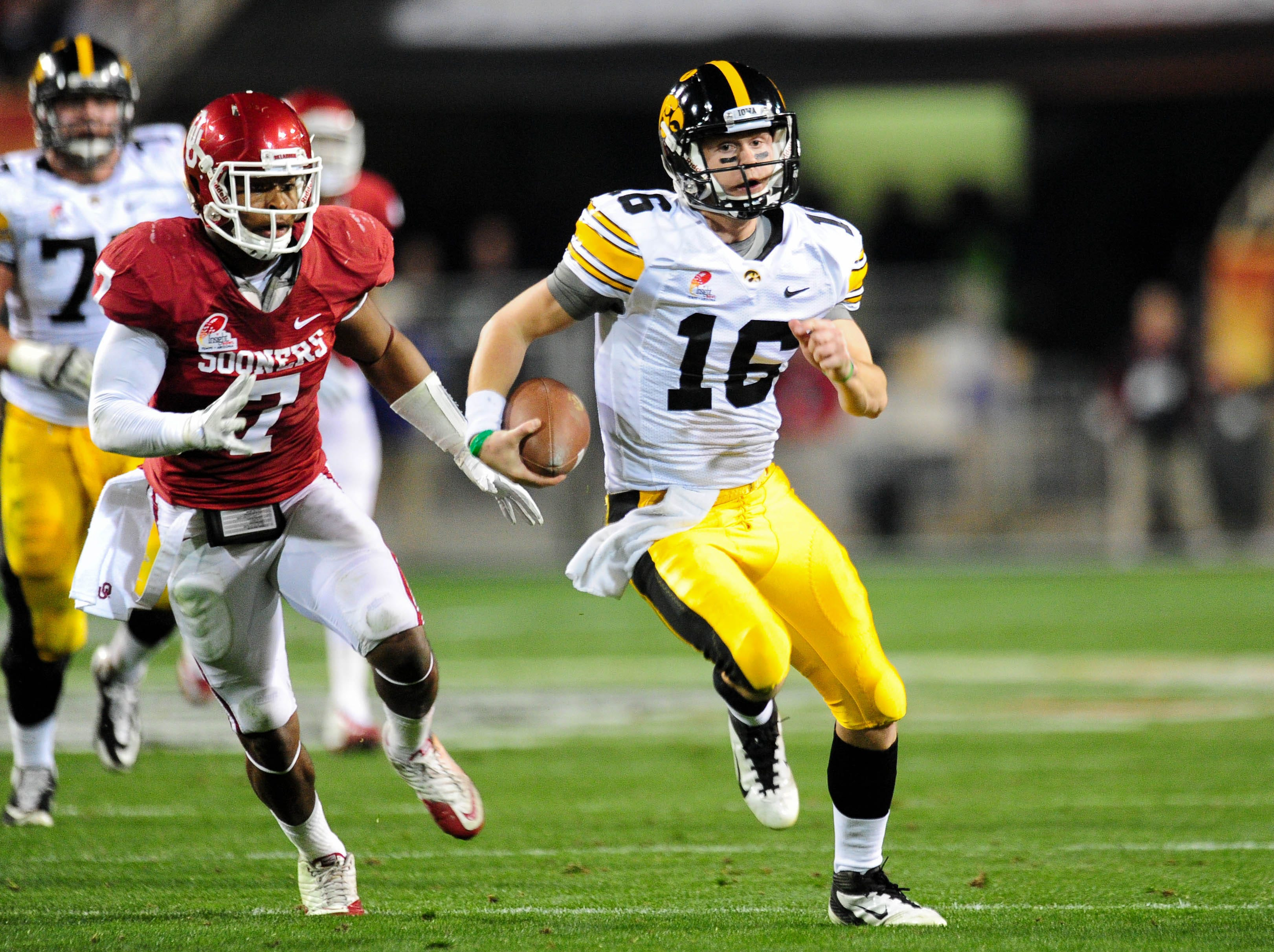 Dec. 30, 2011; Tempe, AZ, USA; Iowa Hawkeyes quarterback James Vandenberg (16) runs for a first down while being pursued by Oklahoma Sooners linebacker Corey Nelson (7) during the first half during  the 2011 Insight Bowl at Sun Devil Stadium.   Mandatory Credit: Matt Kartozian-USA TODAY Sports