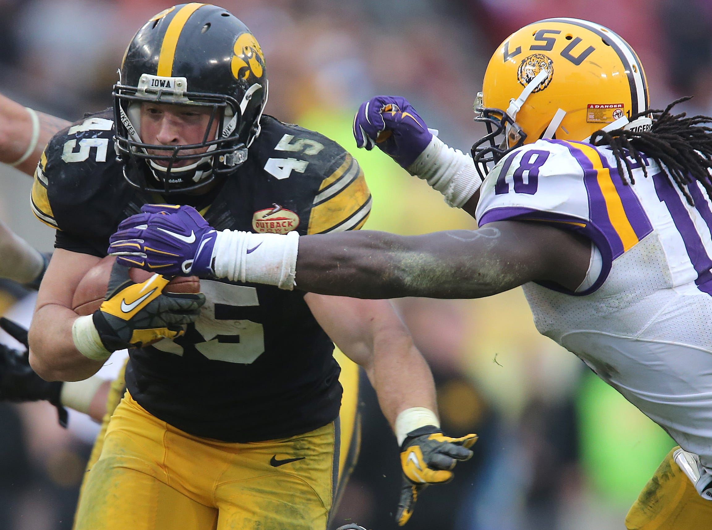 Iowa running back Mark Weisman prepares for the hit by LSU linebacker Lamin Barrow in the Outback Bowl on Wednesday, Jan. 1, 2014, in Tampa, Florida. (Bryon Houlgrave/The Register)