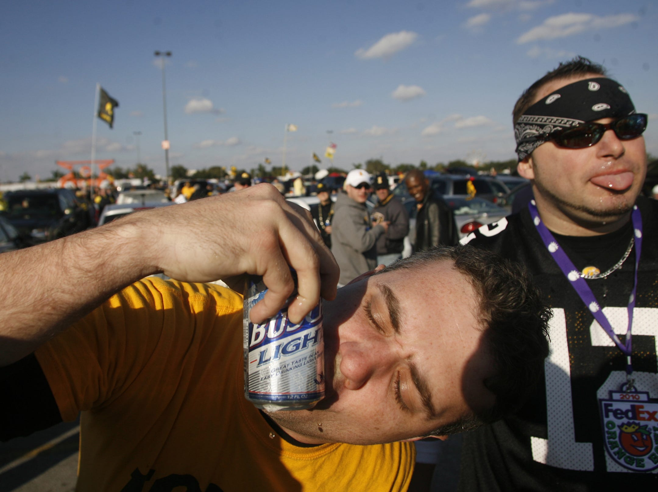 Scott Green, of Fort Lauderdale, and Jason Jefferies, of LaPorte City, Iowa, right, shotgun beers while tailgating before the start of the Orange Bowl, Tuesday, Jan. 5, 2010, at LandShark Stadium, in Miami Gardens, Fl.