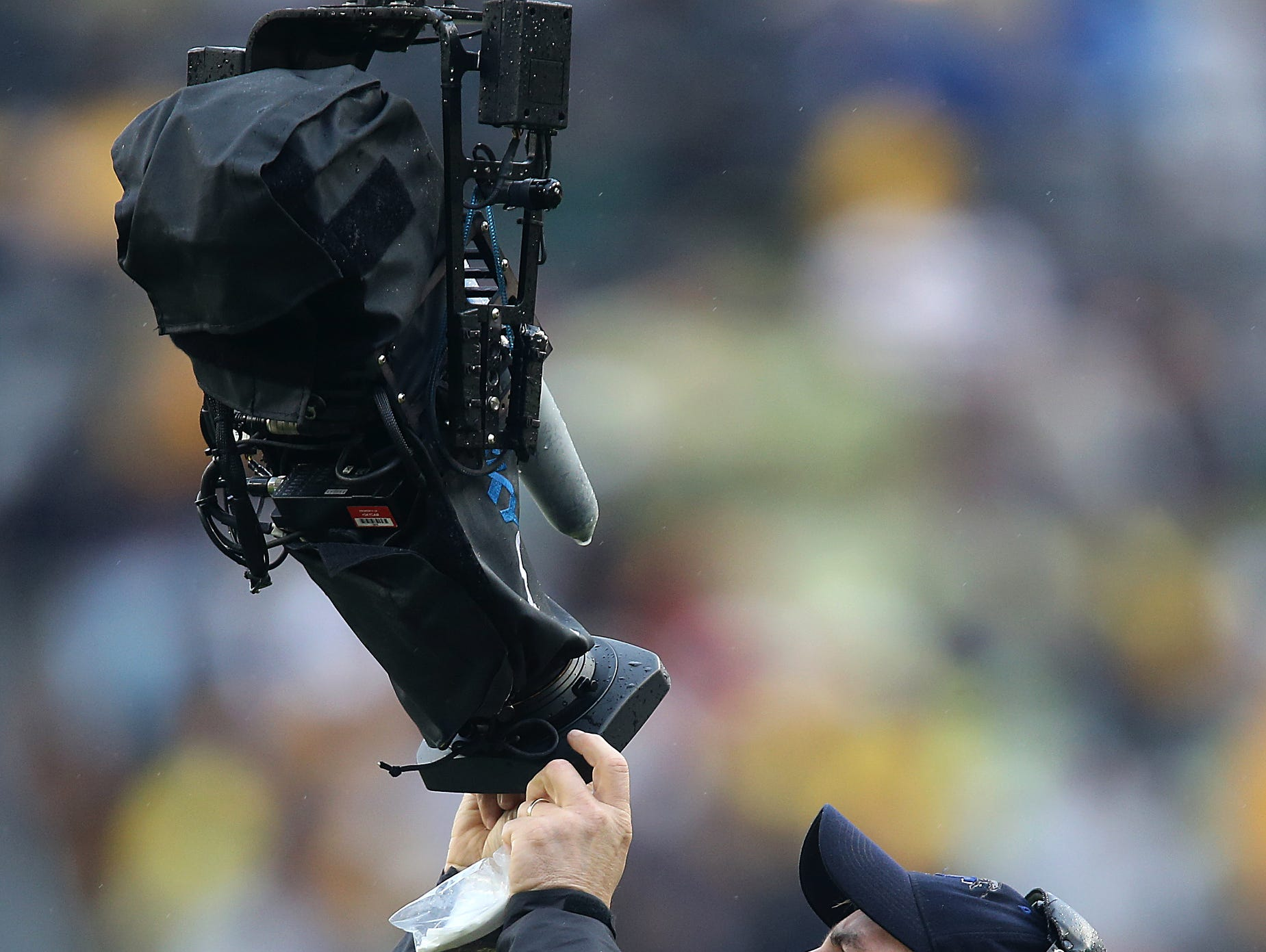 An ESPN camera operator wipes rain away from the lens of the Skycam during a timeout during the 2014 Outback Bowl between Iowa and LSU on Wednesday, Jan. 1, 2014, in Tampa, Florida. (Bryon Houlgrave/The Register)