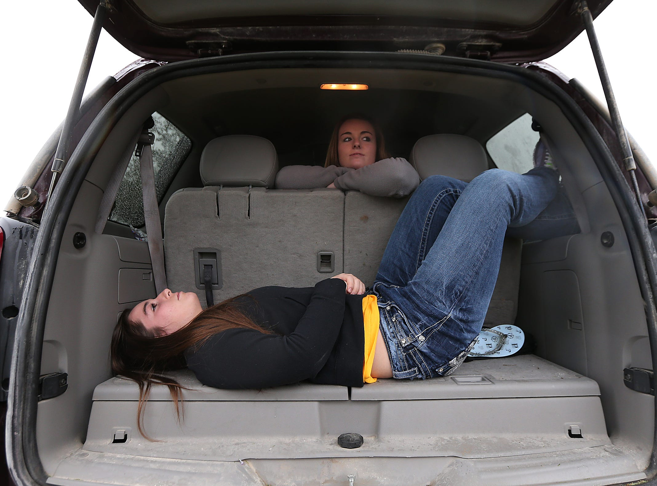 Morgan Nichols, 15, of West Liberty lays down in the back of a van as her sister, Merideth, 18, relaxes in the back prior to the Outback Bowl on Wednesday, Jan. 1, 2014, in Tampa, Florida. (Bryon Houlgrave/The Register)