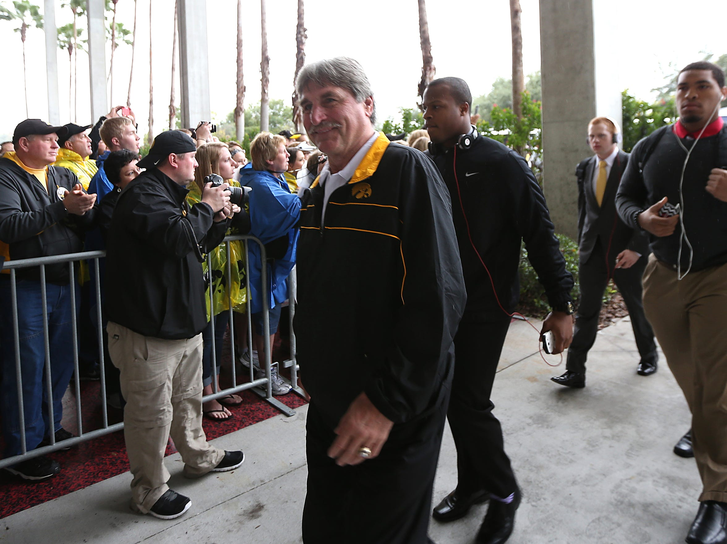 Iowa radio personality and former Hawkeye Ed Podolak makes the walk up to Raymond James Stadium on Wednesday, Jan. 1, 2014, in Tampa, Florida. (Bryon Houlgrave/The Register)