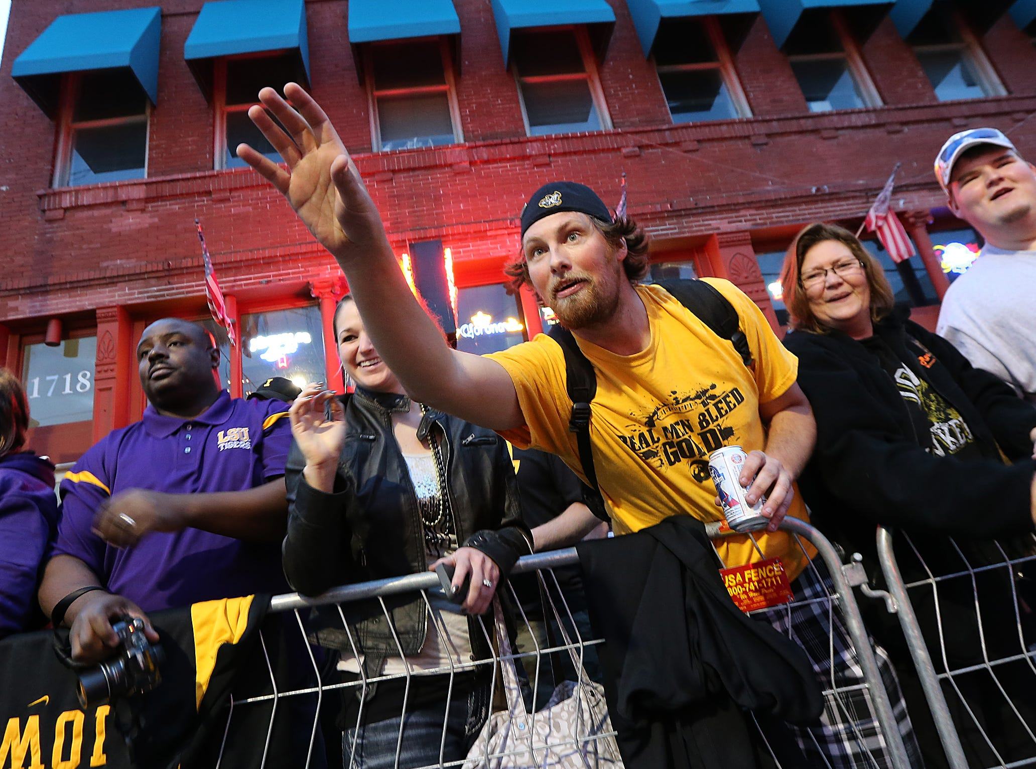 Jim Stephens, a Hawkeye fan from Omaha, reaches out to receive some beads being tossed by parade walkers during the Outback Bowl parade on Tuesday, Dec. 31, 2013, in Tampa, Florida. (Bryon Houlgrave/The Register)