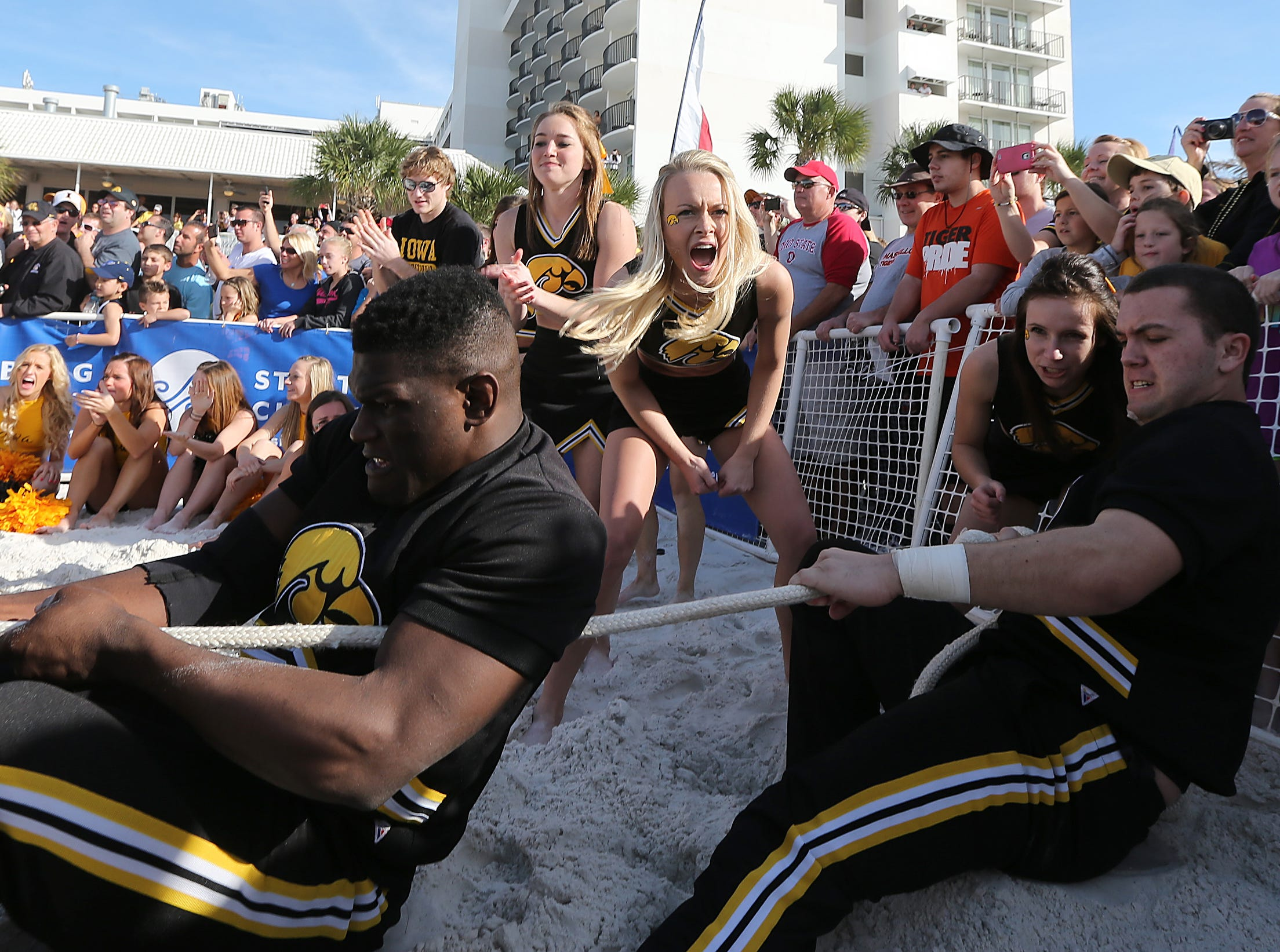 The guys on the Iowa cheerleading team get some encouragement from the girls as they battle LSU's men in a tug-of-war on Monday, Dec. 30, 2013, in Clearwater, Florida. (Bryon Houlgrave/The Register)