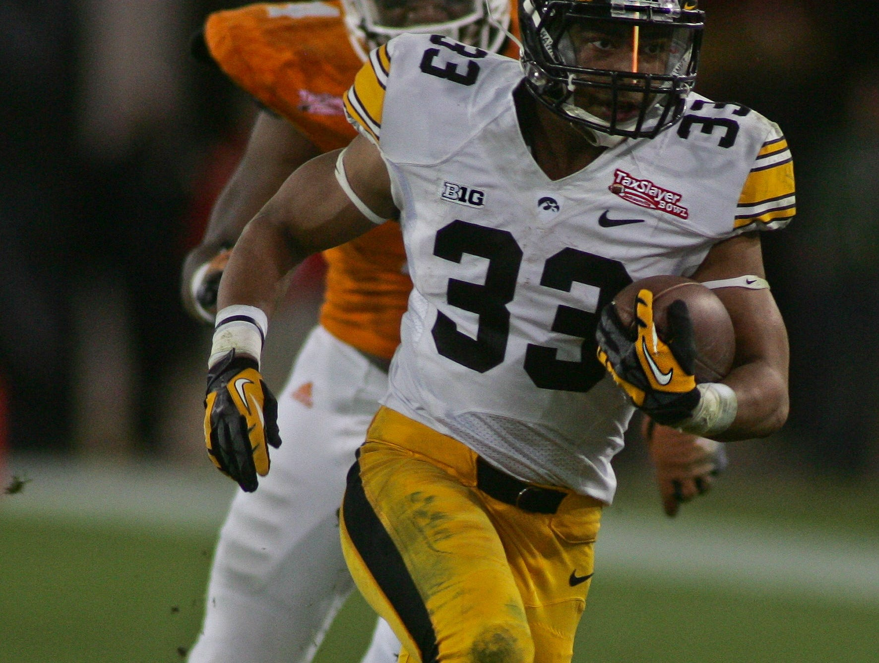 Jan 2, 2015; Jacksonville, FL, USA; Iowa Hawkeyes running back Jordan Canzeri (33) runs for a first down in the third quarter of the 2015 TaxSlayer Bowl against the Tennessee Volunteers at EverBank Field. The Tennessee Volunteers beat the Iowa Hawkeyes 45-28. Mandatory Credit: Phil Sears-USA TODAY Sports