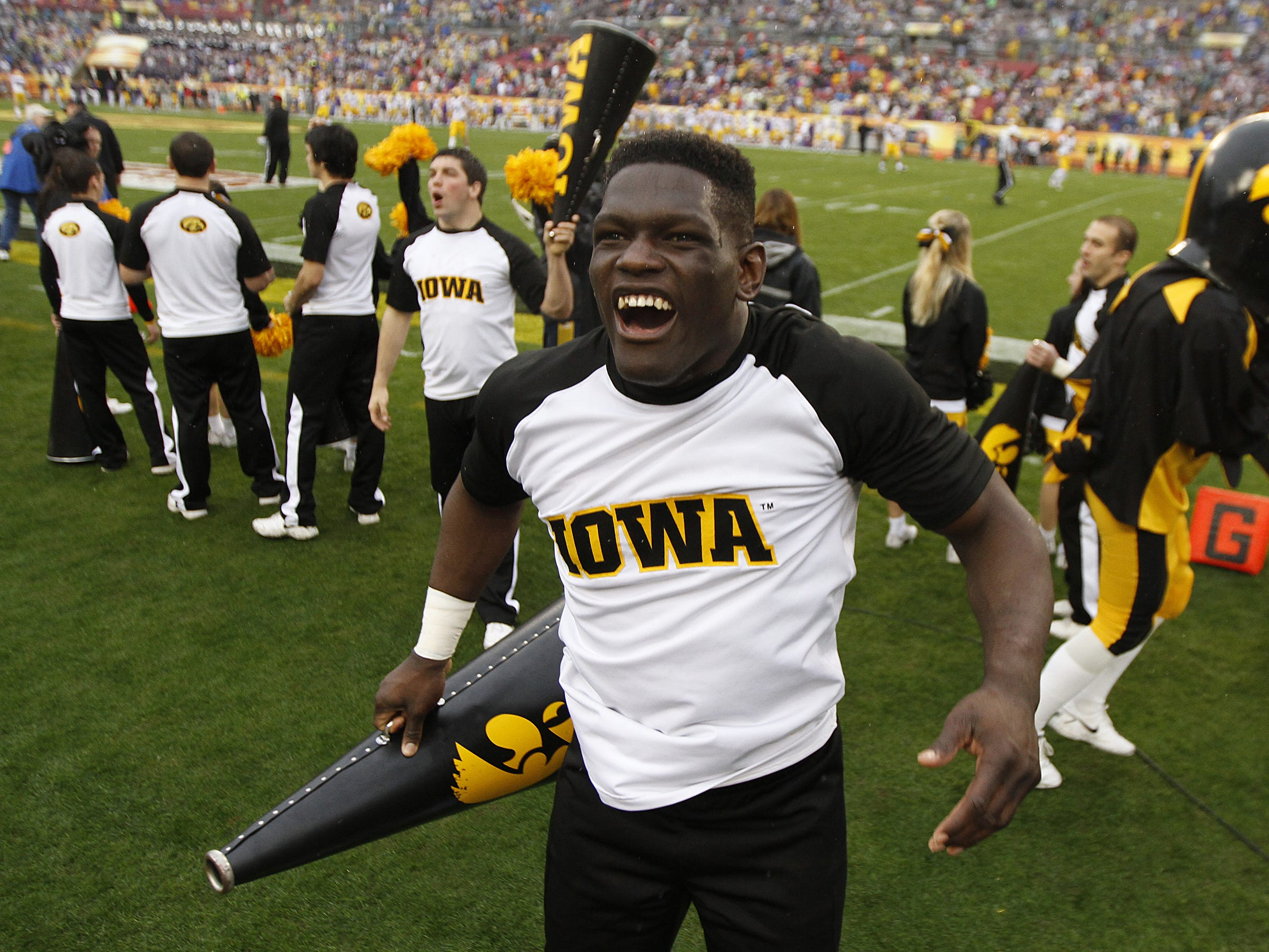 Iowa spirit squad member Oz Agbese, a Waterloo East grad, gets the Iowa crowd fired up prior to the start of the Outback Bowl against LSU on Wednesday, Jan. 1, 2014, in Tampa, Florida. (Bryon Houlgrave/The Register)