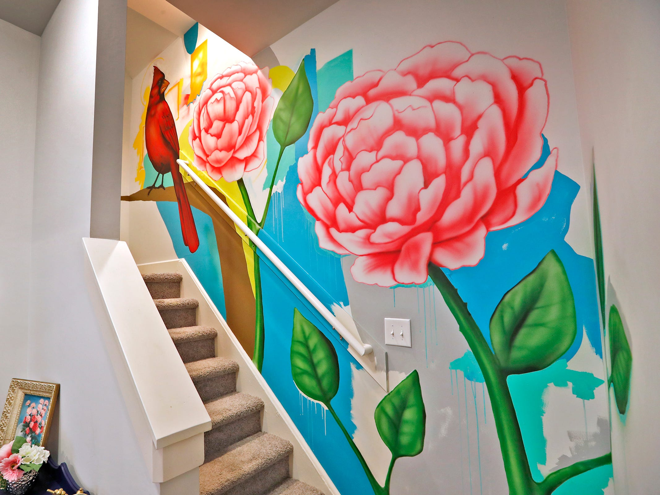 AirBnb owner Felicia Kiesel loves Indianapolis and uses items throughout the rental that remember the city, at 804 N. Keystone Ave., Monday, Dec. 3, 2018, including this mural with the state bird, the cardinal, and flower, the peony.