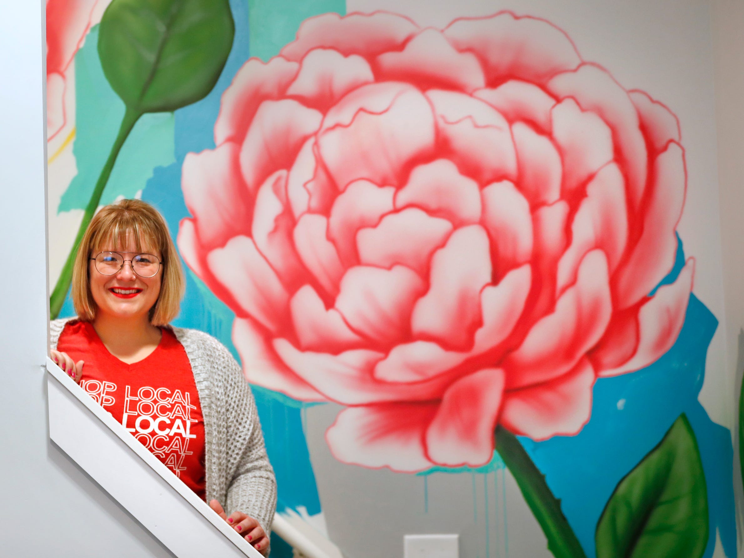 AirBnb owner Felicia Kiesel loves Indianapolis and uses items throughout the rental that remember the city, at 804 N. Keystone Ave., Monday, Dec. 3, 2018, including this mural with the state bird and flower, right, the peony.