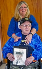 Kathy Rinks stands with her father, Curtis Willis, as he shows a photo of himself when he was in the Army, Friday, Nov. 30, 2018.  Willis is a former boxer and double Purple Heart recipient from when he was a medic in the Korean War.