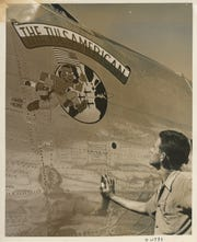 Man looks at Tulsamerican nose art, signatures visible on the side of the plane.