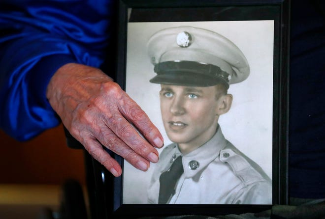 Curtis Willis shows a photo of himself when he was in the Army, Friday, Nov. 30, 2018.  Willis is a former boxer and double Purple Heart recipient from when he was a medic in the Korean War.