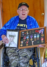 Curtis Willis shows an old photo of himself when he was in the Army, and a display of his medals, Friday, Nov. 30, 2018.  Willis is a former boxer and double Purple Heart recipient from when he was a medic in the Korean War.