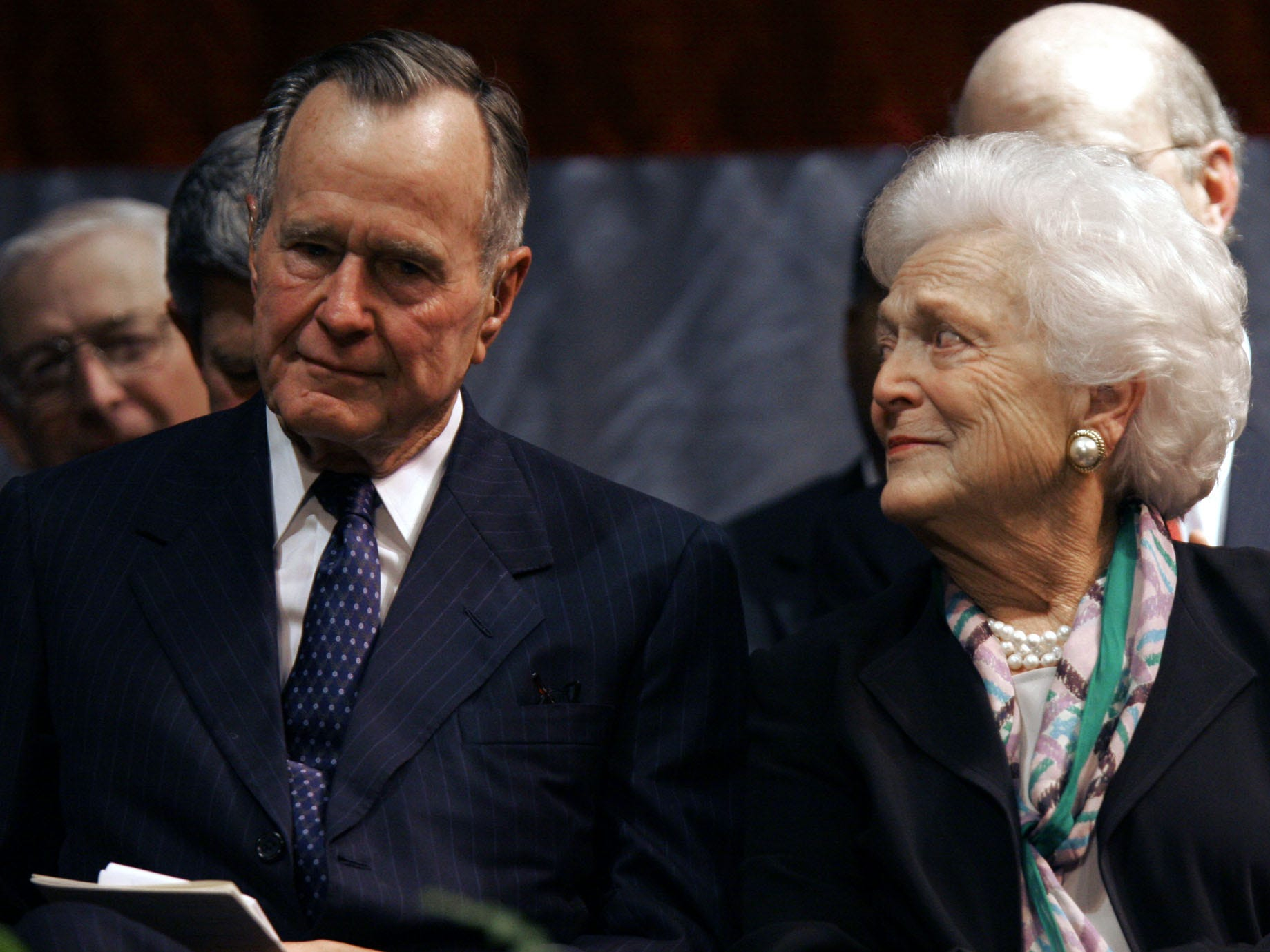 "Former President George H. W. Bush, left, and his wife Barbara Bush listen to one of the eulogies praising longtime family friend and former Mississippi congressman, G.V. ""Sonny"" Montgomery, at the Temple Theater in Meridian, Miss., Tuesday, May 16, 2006, during Montgomery's public funeral."